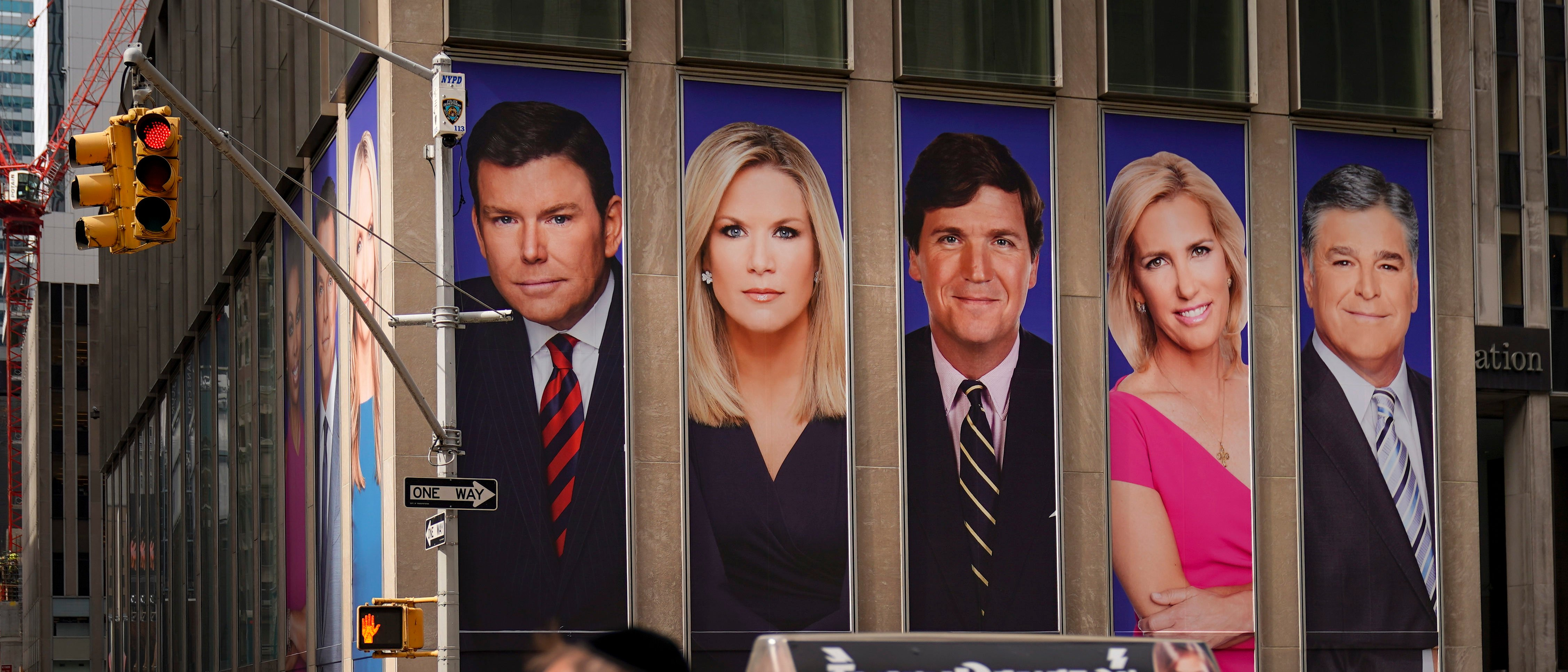 Traffic on Sixth Avenue passes by advertisements featuring Fox News personalities, including Bret Baier, Martha MacCallum, Tucker Carlson, Laura Ingraham, and Sean Hannity, adorn the front of the News Corporation building, March 13, 2019 in New York City. (Drew Angerer/Getty Images)