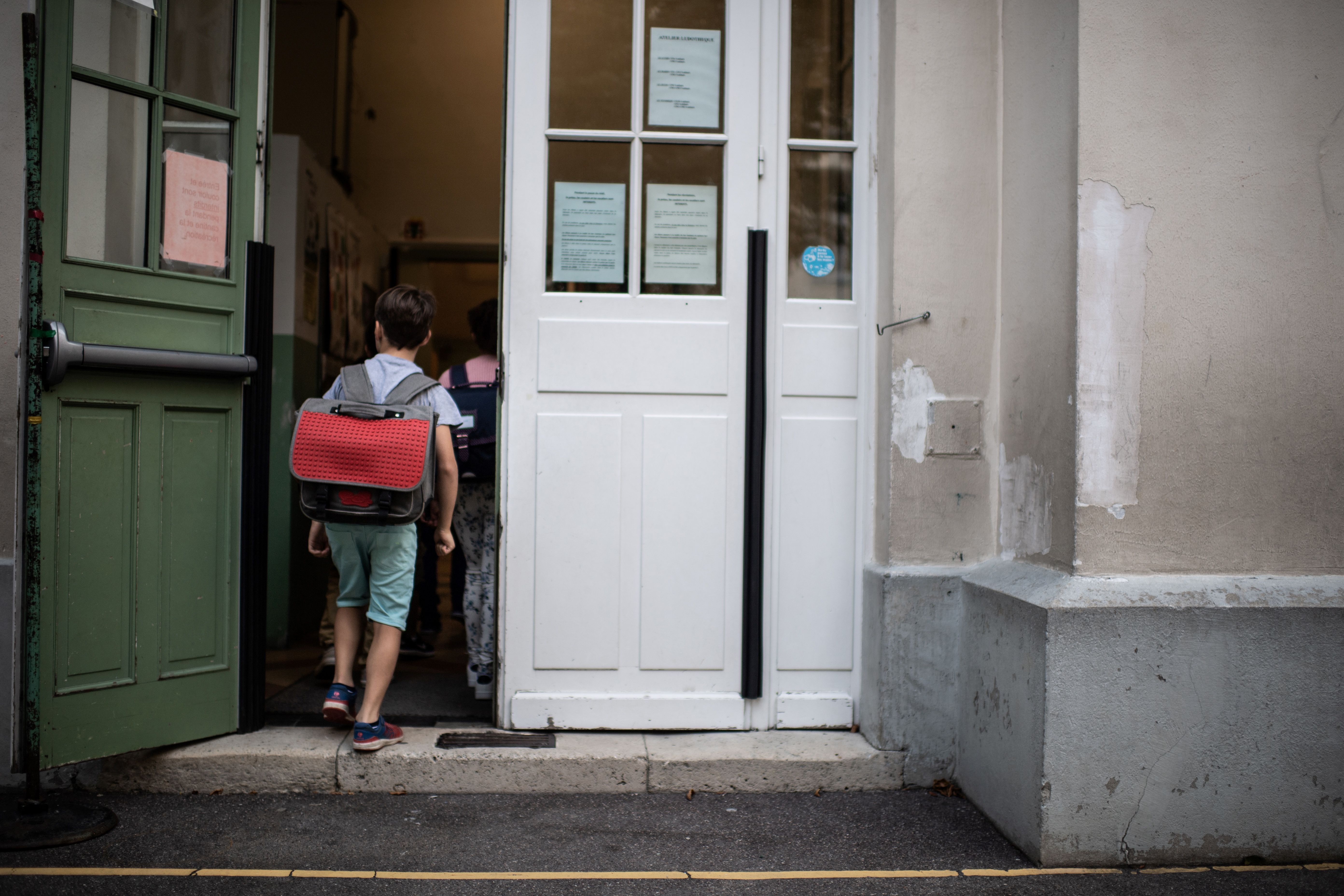A boy enters in his classroom on the first day of the start of the school year, at the Chaptal elementary school in Paris. (MARTIN BUREAU/AFP via Getty Images)