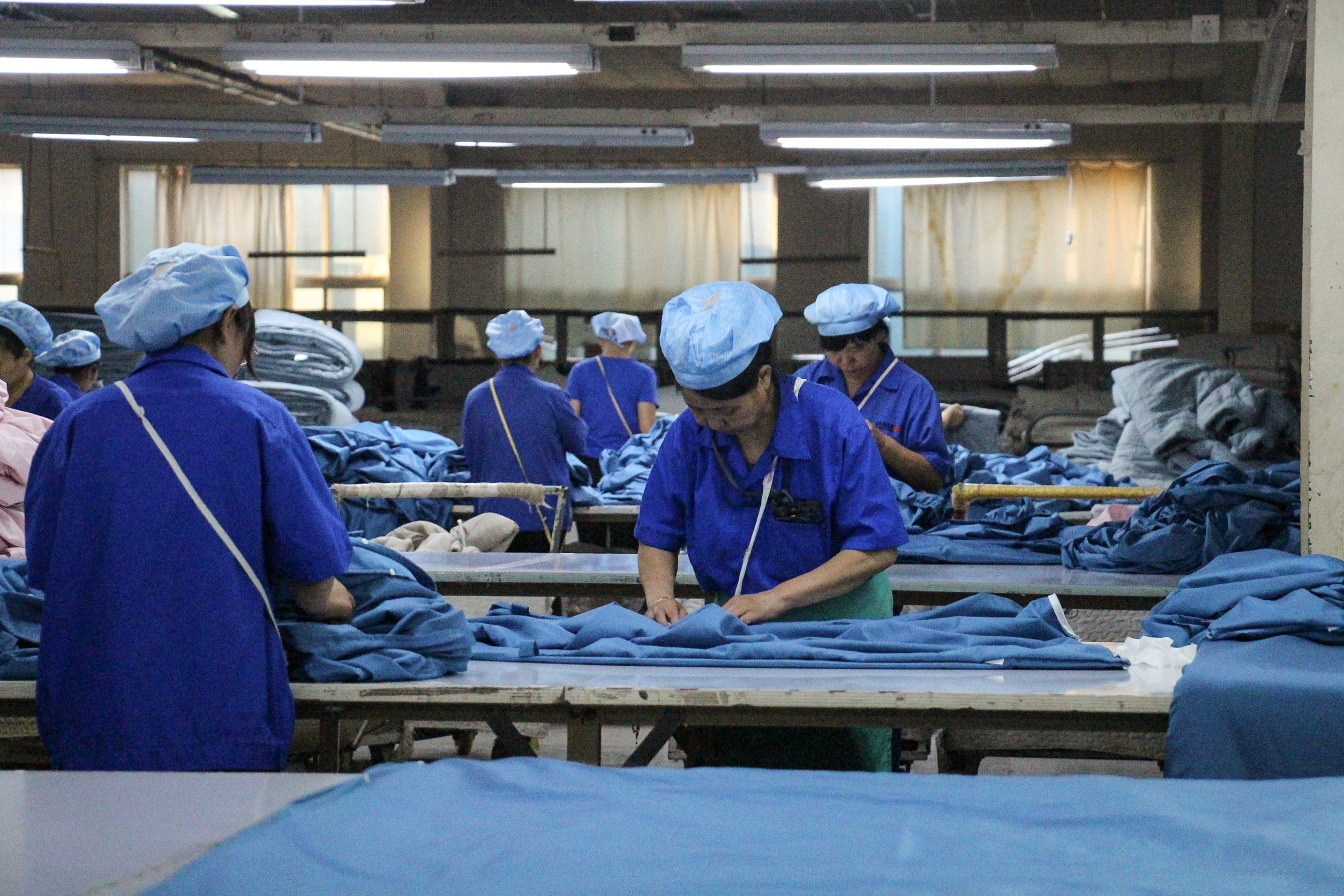 This photo taken on August 29, 2019 shows workers producing cloth that will be exported to the US at a textile factory in Binzhou, China's eastern Shandong province. (STR/AFP via Getty Images)