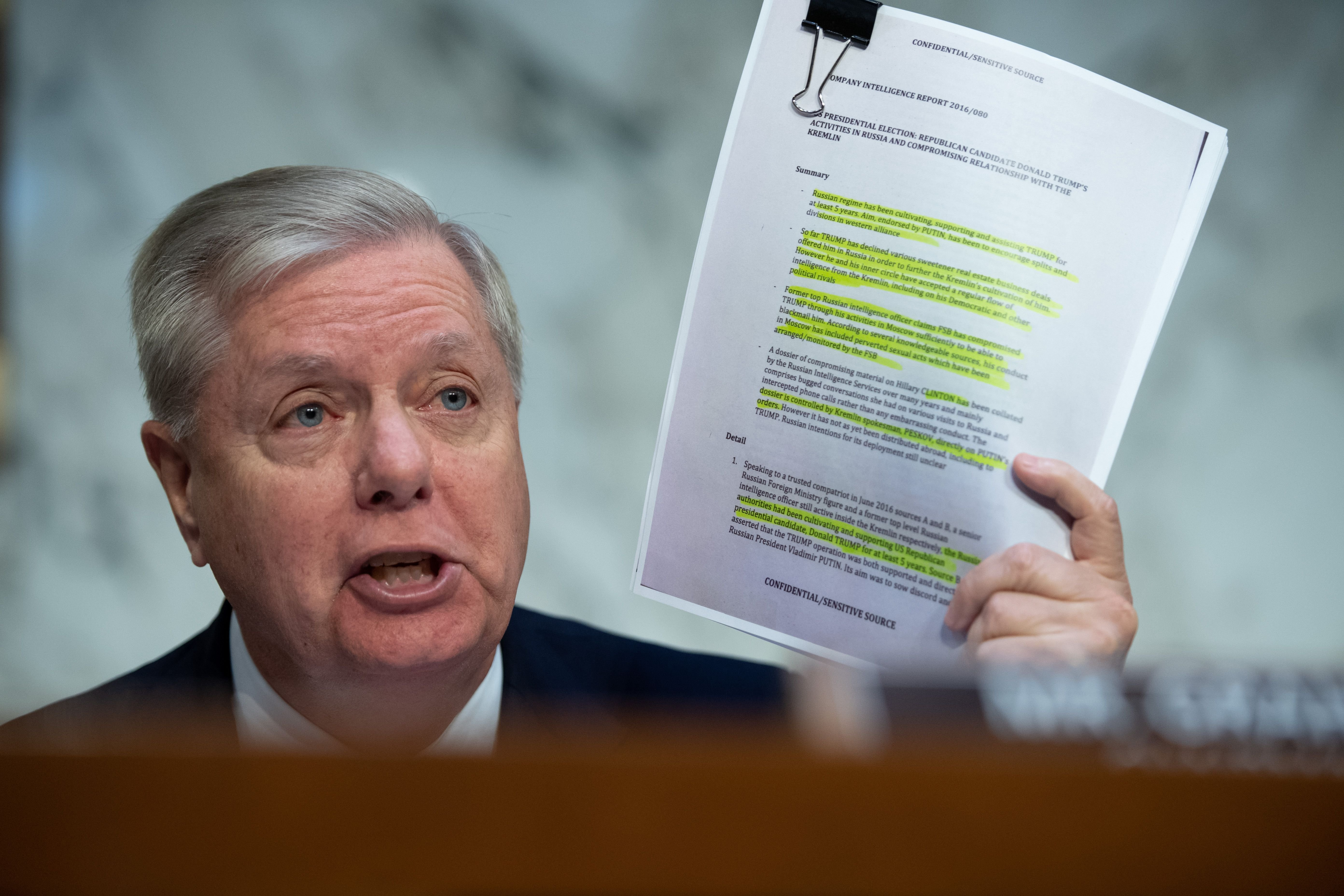 Chairman of the Senate Judiciary Committee Lindsey Graham, Republican of South Carolina, holds a copy of the Steele Dossier, as Justice Department Inspector General Michael Horowitz testifies about the Inspector General's report on alleged abuses of the Foreign Intelligence Surveillance Act (FISA). (SAUL LOEB/AFP via Getty Images)
