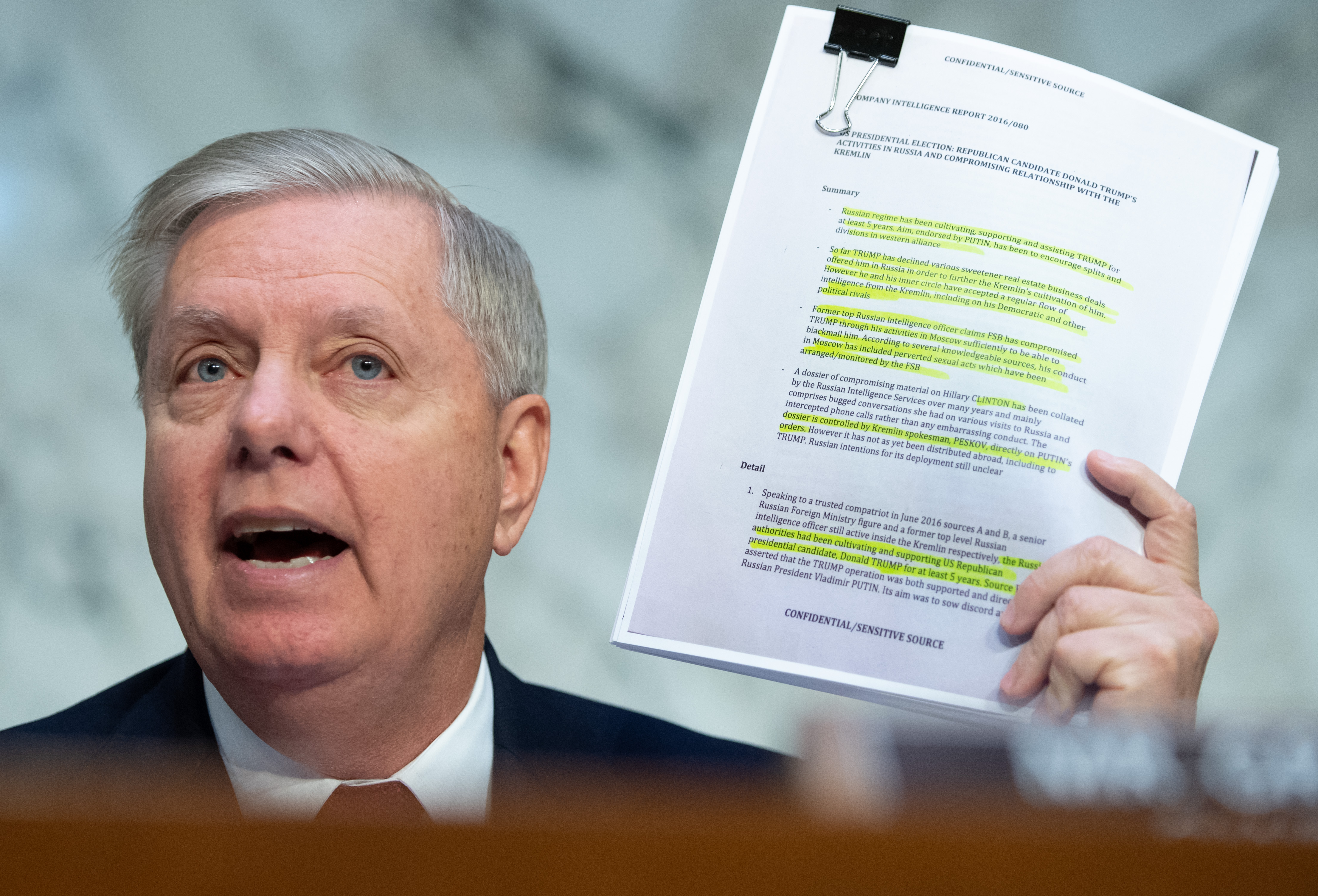 Chairman of the Senate Judiciary Committee Lindsey Graham, Republican of South Carolina, holds a copy of the Steele Dossier, as Justice Department Inspector General Michael Horowitz testifies about the Inspector General's report on alleged abuses of the Foreign Intelligence Surveillance Act (FISA) during a Senate Judiciary Committee hearing on Capitol Hill in Washington, DC, December 11, 2019. (SAUL LOEB/AFP via Getty Images)
