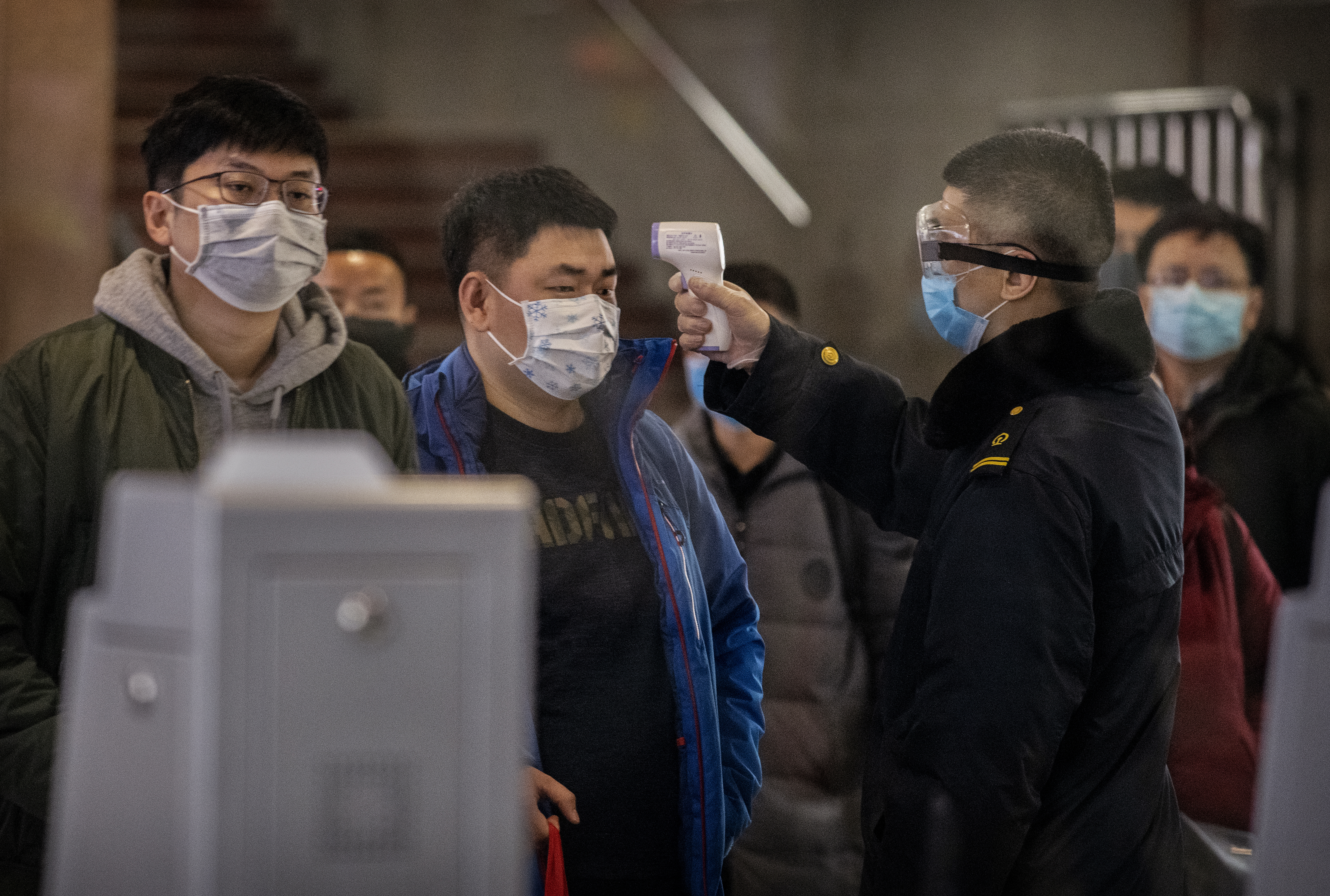 A Chinese passenger that just arrived on the last bullet train from Wuhan to Beijing is checked for a fever by a health worker at a Beijing railway station on January 23, 2020. (Photo by Kevin Frayer/Getty Images)
