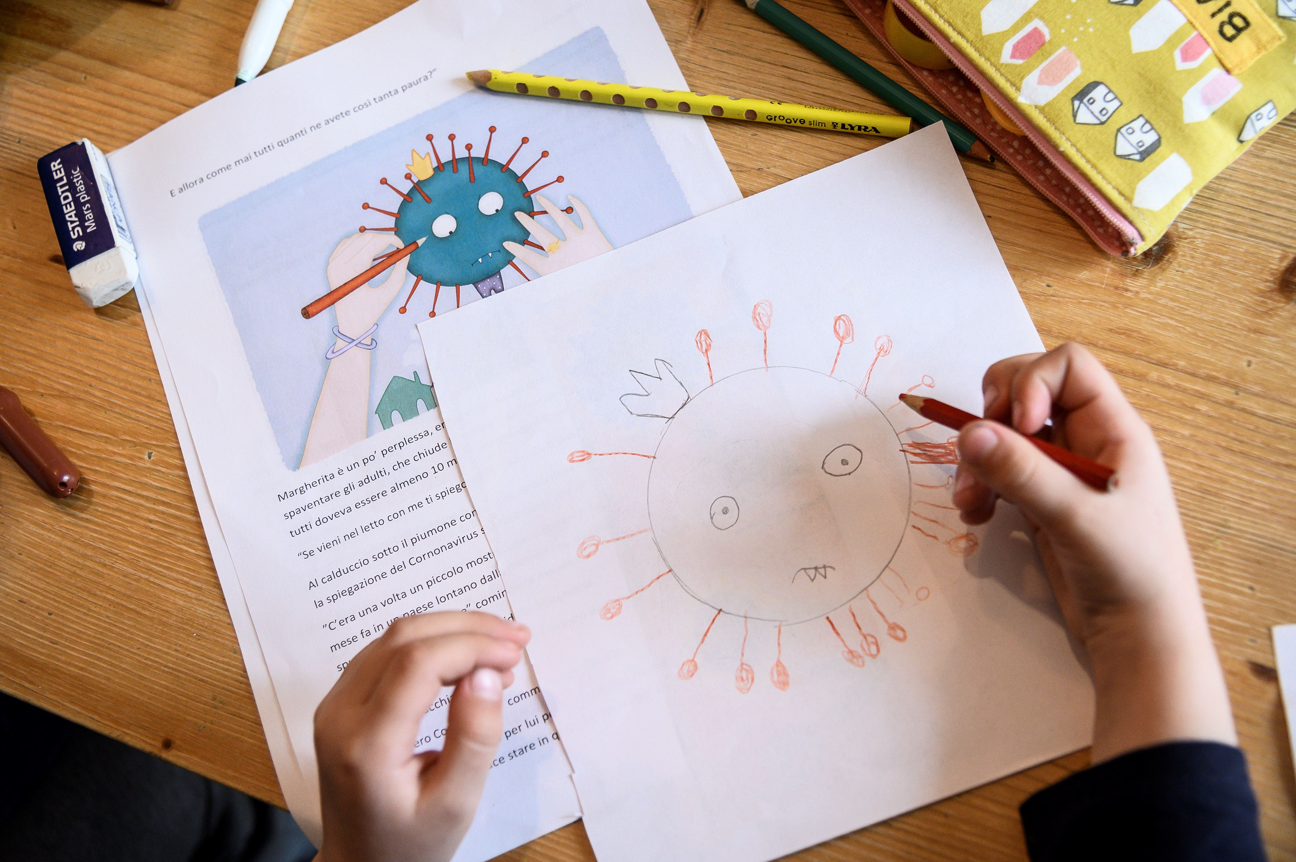 A child draws a COVID-19 coronavirus as part of school homeworks. (Photo by MARCO BERTORELLO/AFP via Getty Images)