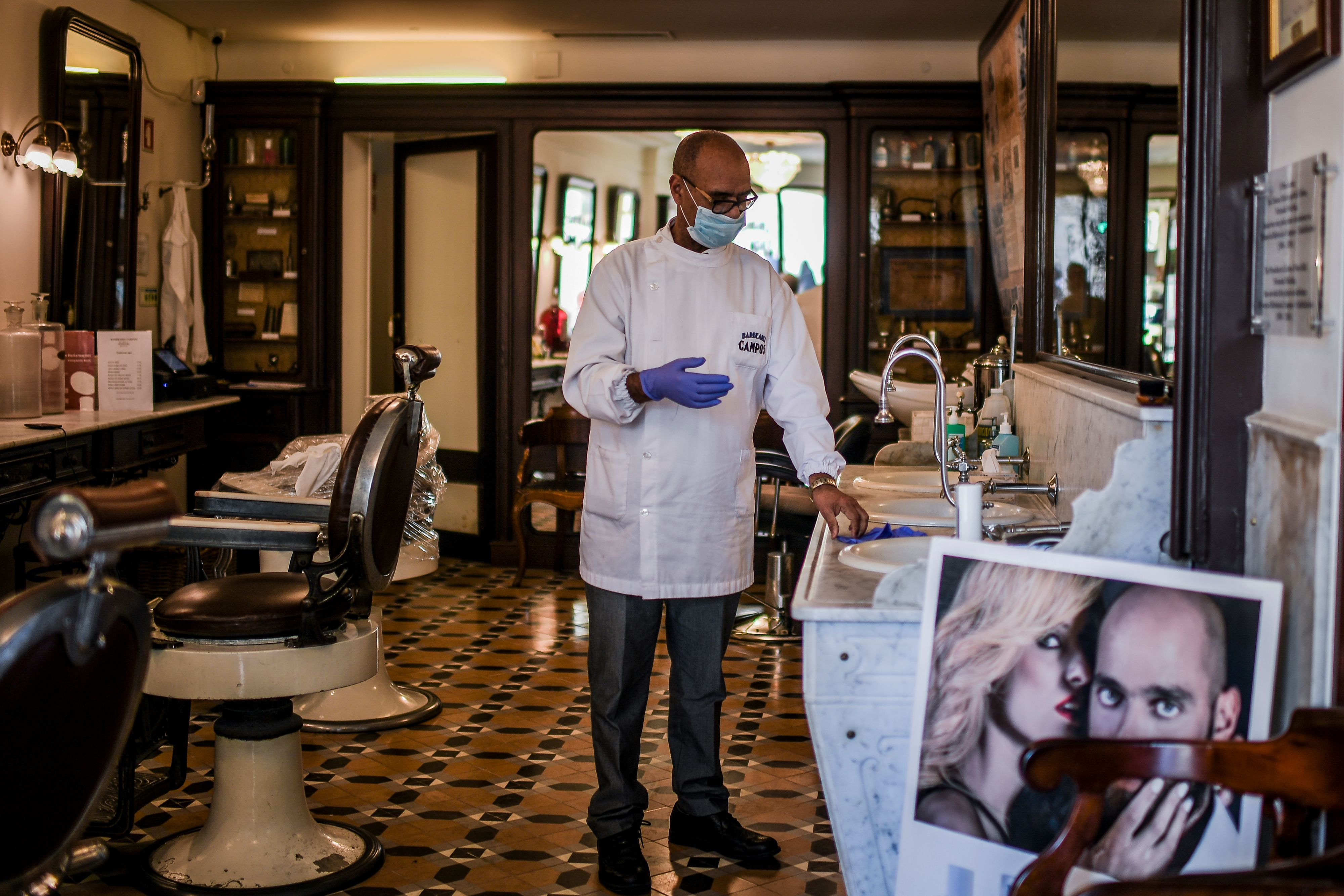 Portuguese barber Elizio da Silva Gomes wearing a protective mask puts on his gloves at the Campos barbershop in Lisbon on March 12, 2020. ( PATRICIA DE MELO MOREIRA/AFP via Getty Images)