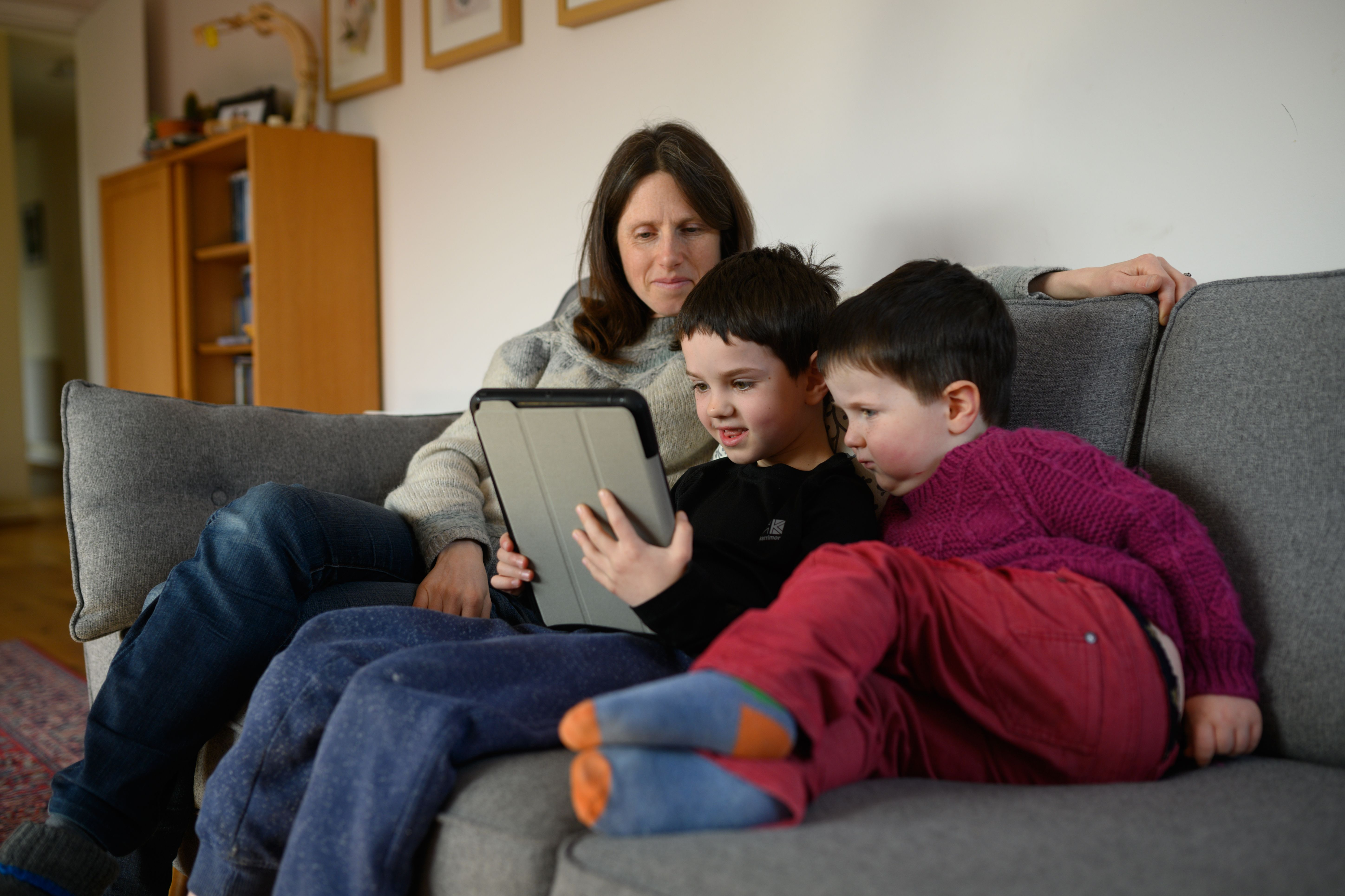 Mother and two children navigate online learning resources provided by their infant school in the village of Marsden, near Huddersfield, northern England. (Photo by OLI SCARFF/AFP via Getty Images)