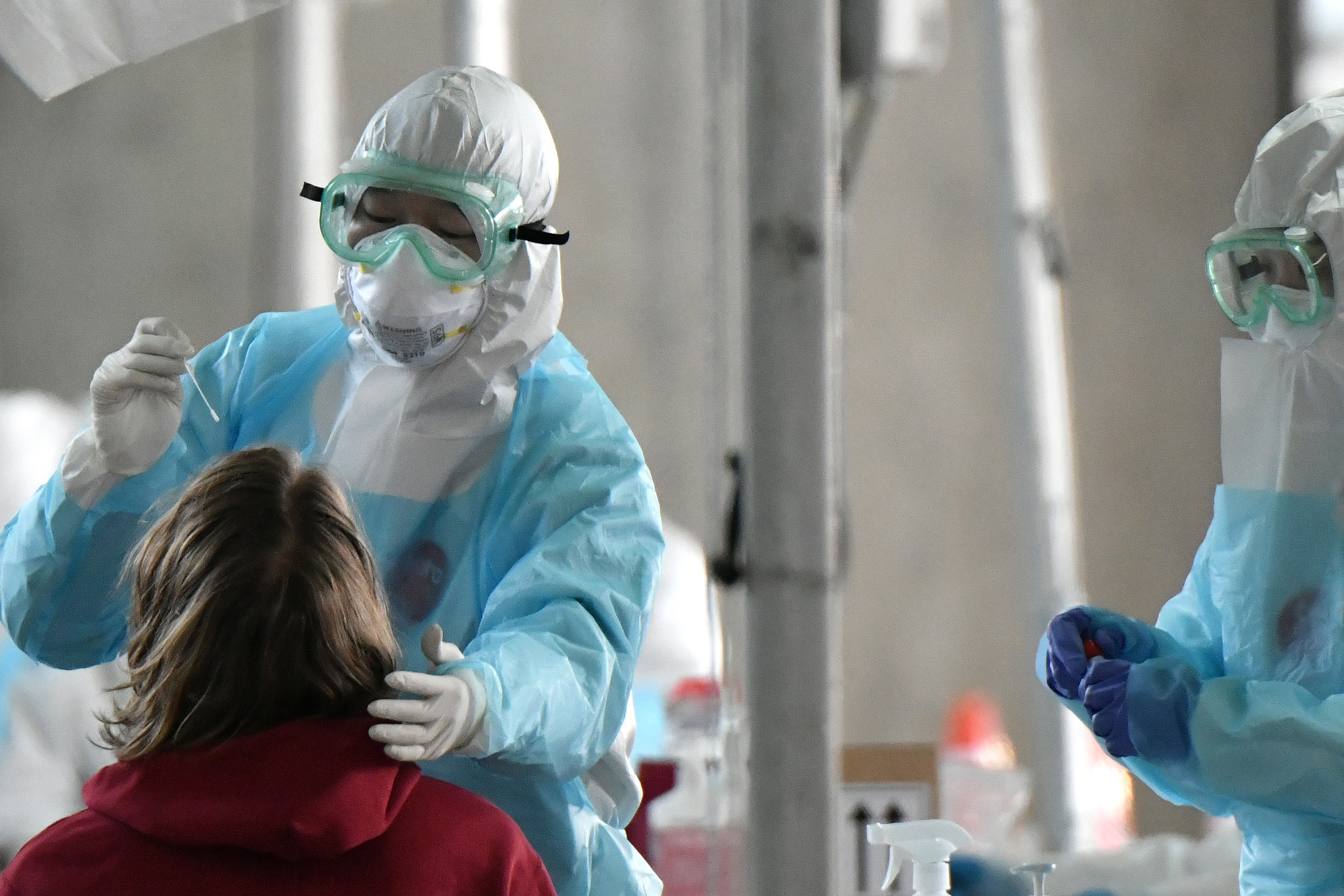 A medical staff wearing protective clothing takes test samples for the COVID-19 coronavirus from a foreign passenger at a virus testing booth outside Incheon international airport, west of Seoul, on April 1, 2020. (JUNG YEON-JE/AFP via Getty Images)