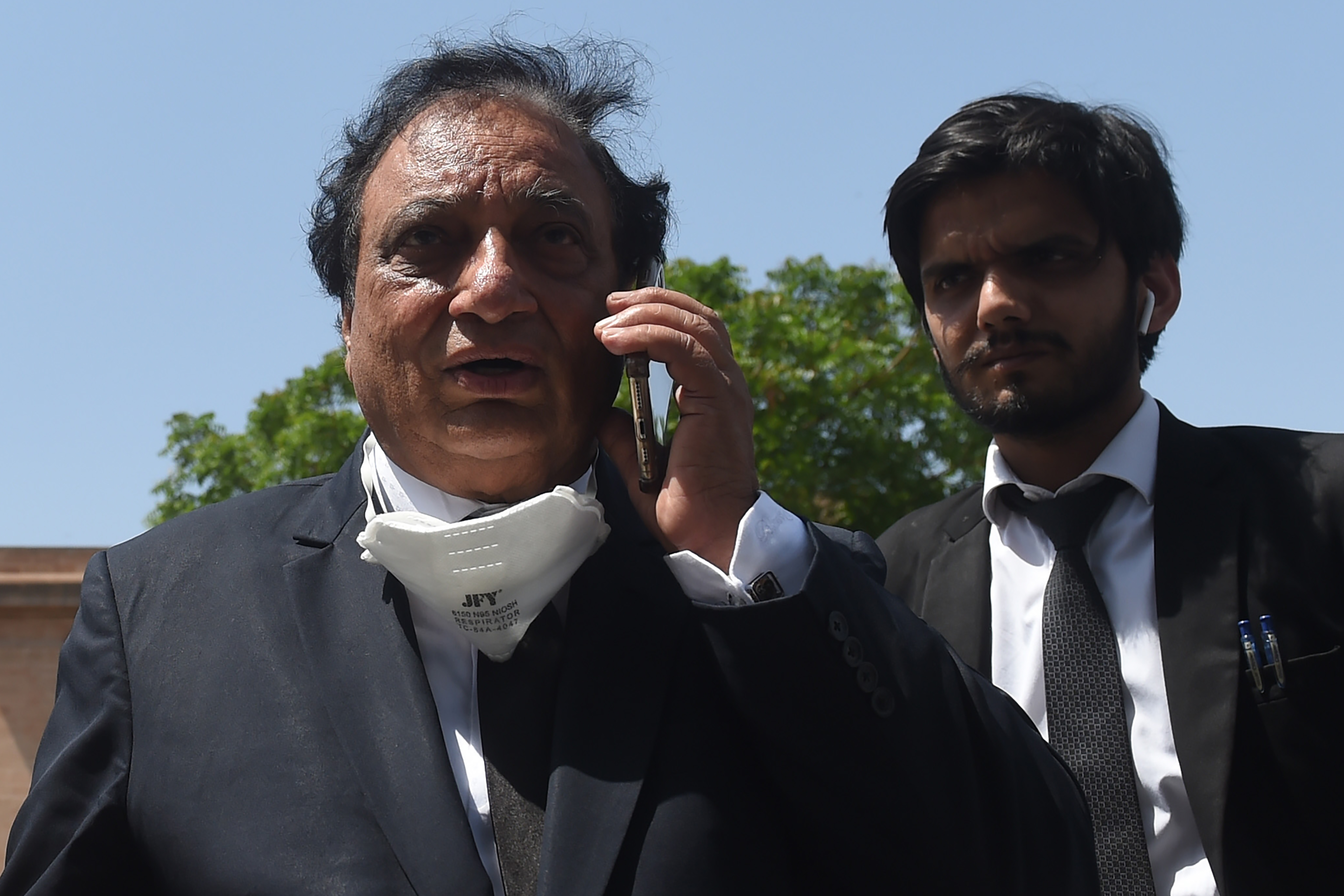 Khawja Naveed (L), defence lawyer of Omar Sheikh, who was convicted to death sentence over the killing of US journalist Daniel Pearl, speaks on his cellphone outside the High Court builiding in Karachi(Photo by ASIF HASSAN/AFP via Getty Images)