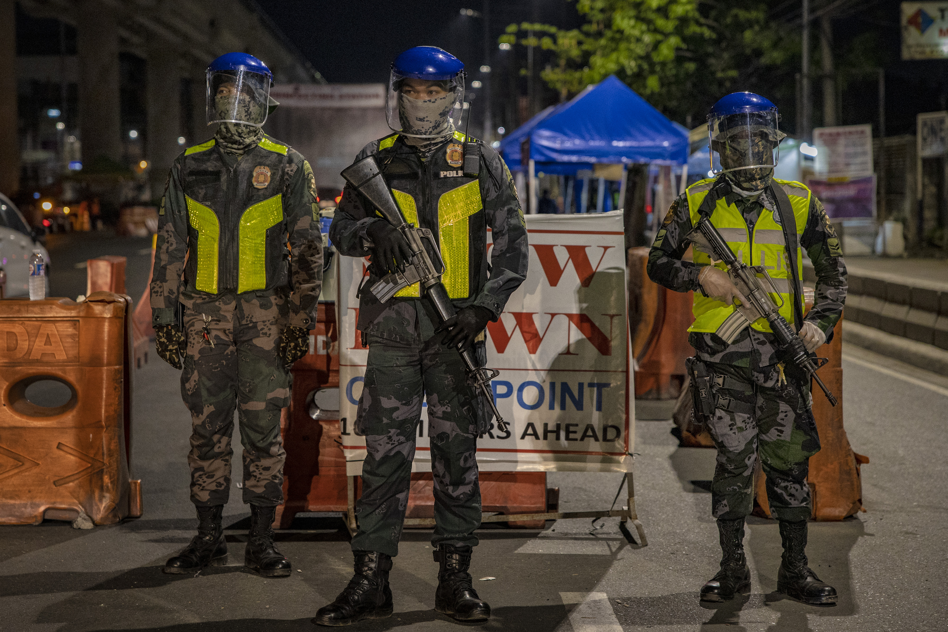 Policemen wearing face shields man a quarantine checkpoint on April 2, 2020 in Marikina, Metro Manila, Philippines. (Photo by Ezra Acayan/Getty Images)