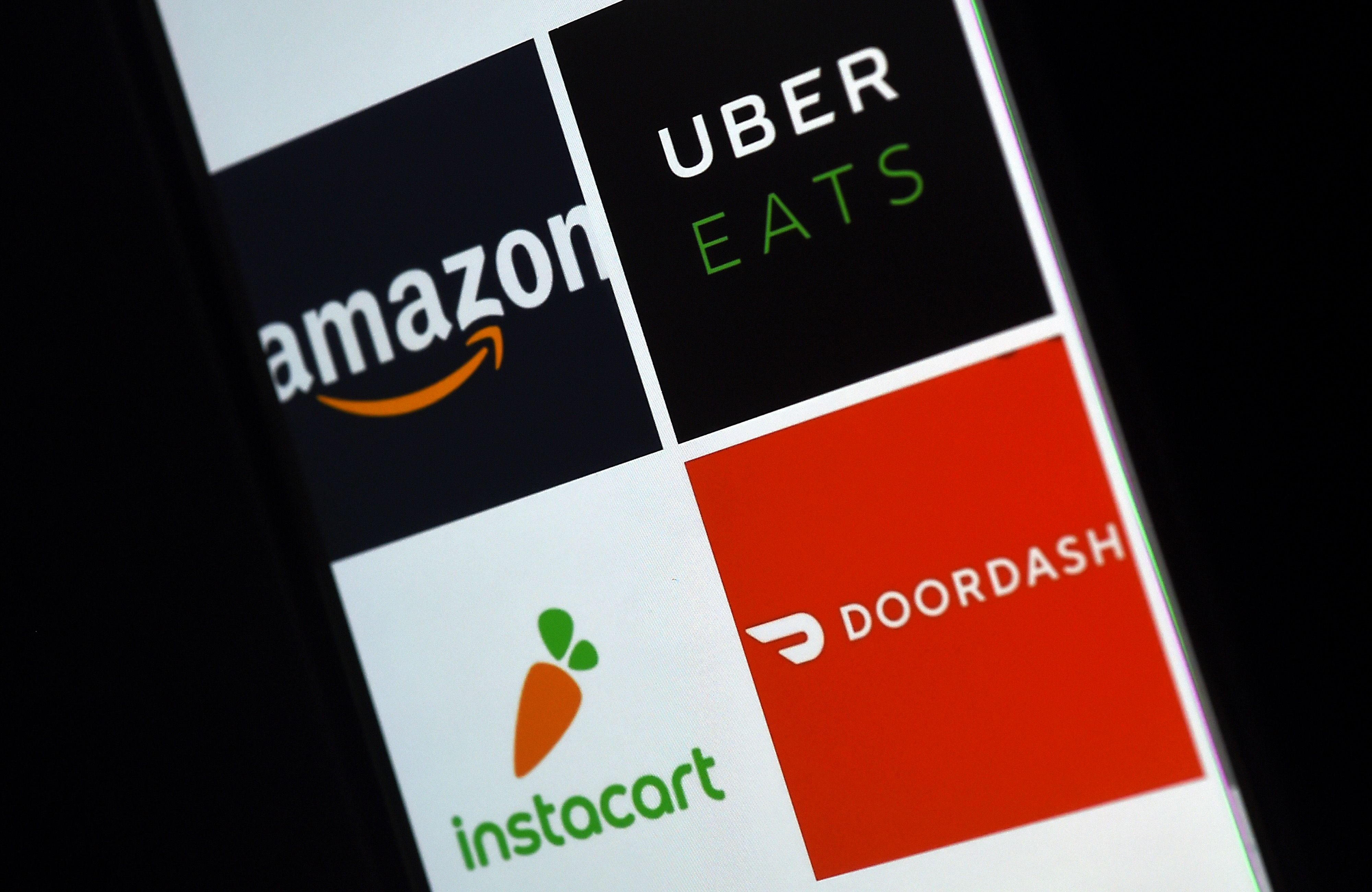 This illustration picture shows delivery applications logos from Amazon, Uber Eats, Instacart and Doordash (OLIVIER DOULIERY/AFP via Getty Images)