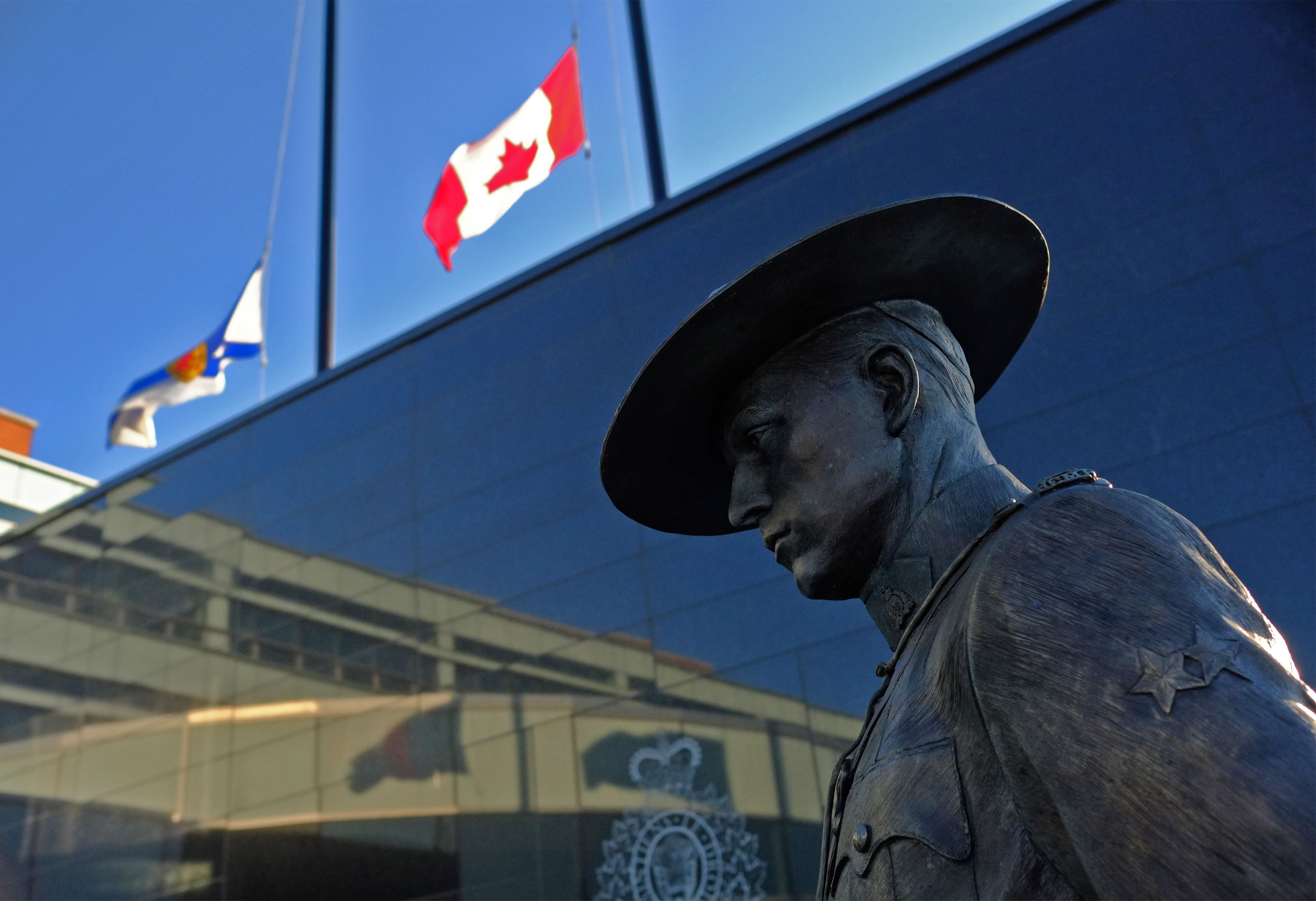 Flags of Nova Scotia and Canada fly at half-staff outside the Nova Scotia Royal Canadian Mounted Police (RCMP) headquarters in Dartmouth, Nova Scotia, Canada, on April 19, 2020, after a shooting rampage left at least 10 dead. (TIM KROCHAK/AFP via Getty Images)