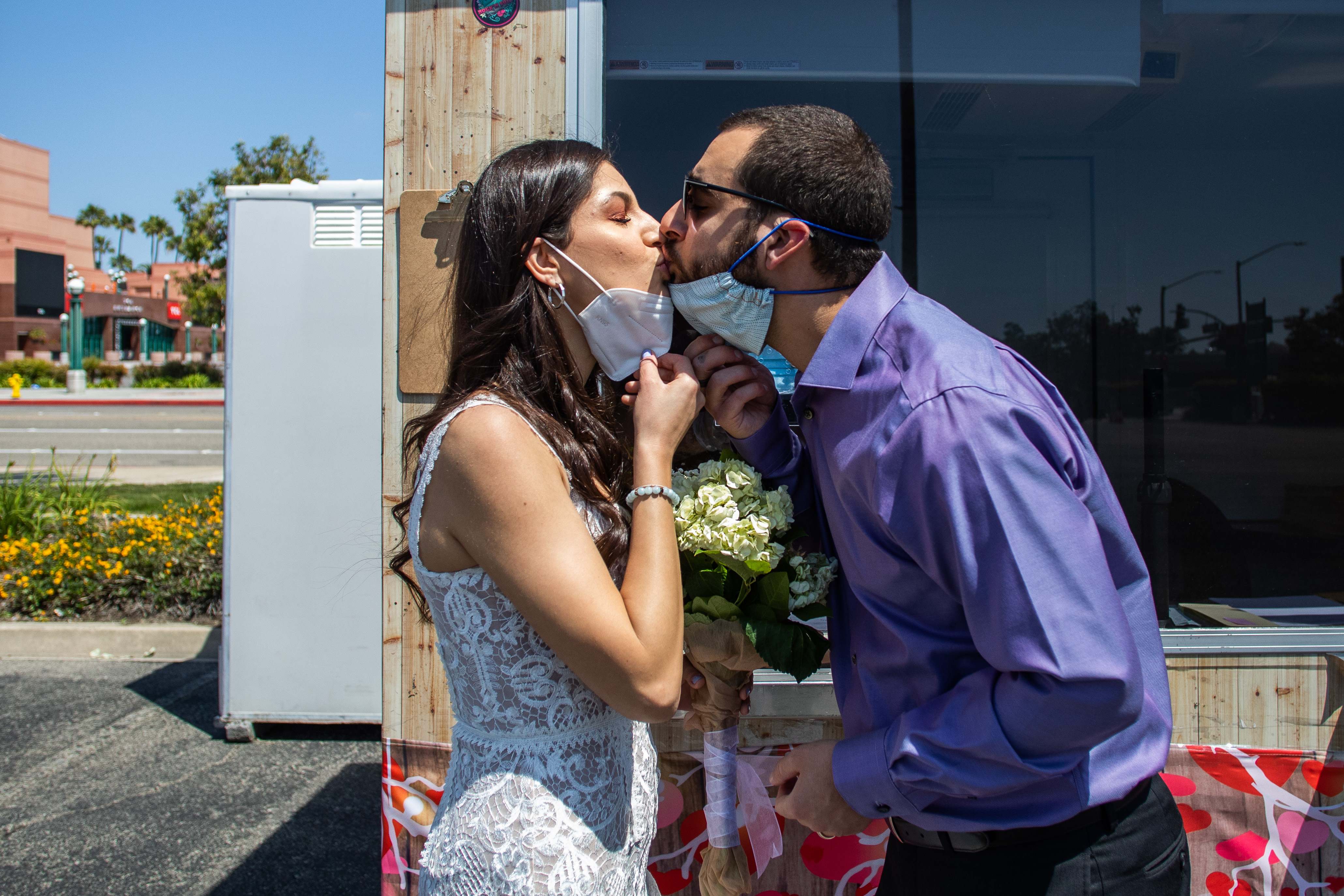 Tiffany McCaryan (L) and Kev McCaryan take off their face masks to kiss after they were married by a clerk recorder at the Honda Center parking lot on April 21, 2020 in Anaheim, California. (Photo by APU GOMES/AFP via Getty Images)