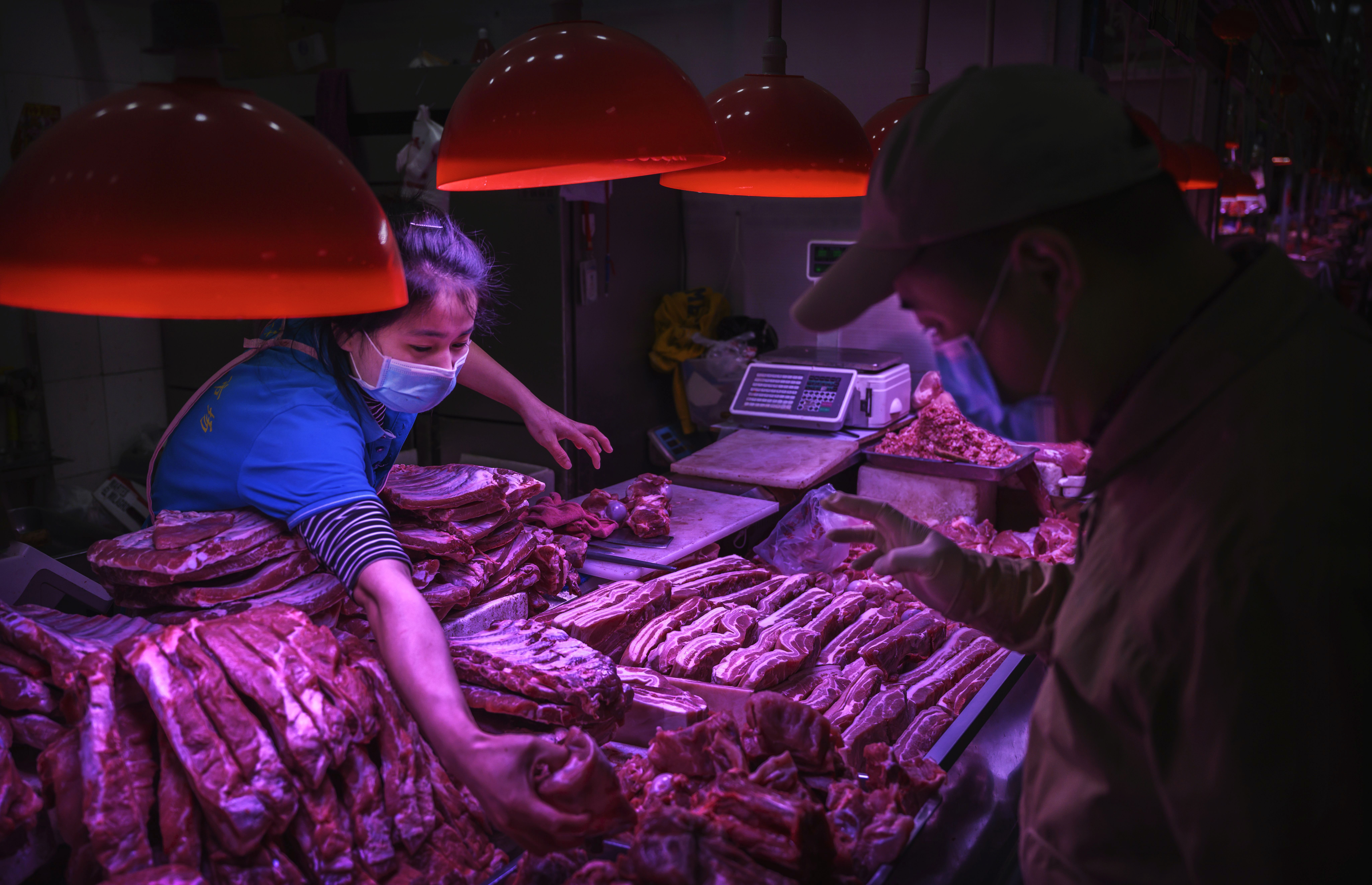 A Chinese meat vendor wears a protective mask as she serves a customer at her stall at a food market on April 24, 2020 in Beijing, China. (Photo by Kevin Frayer/Getty Images)