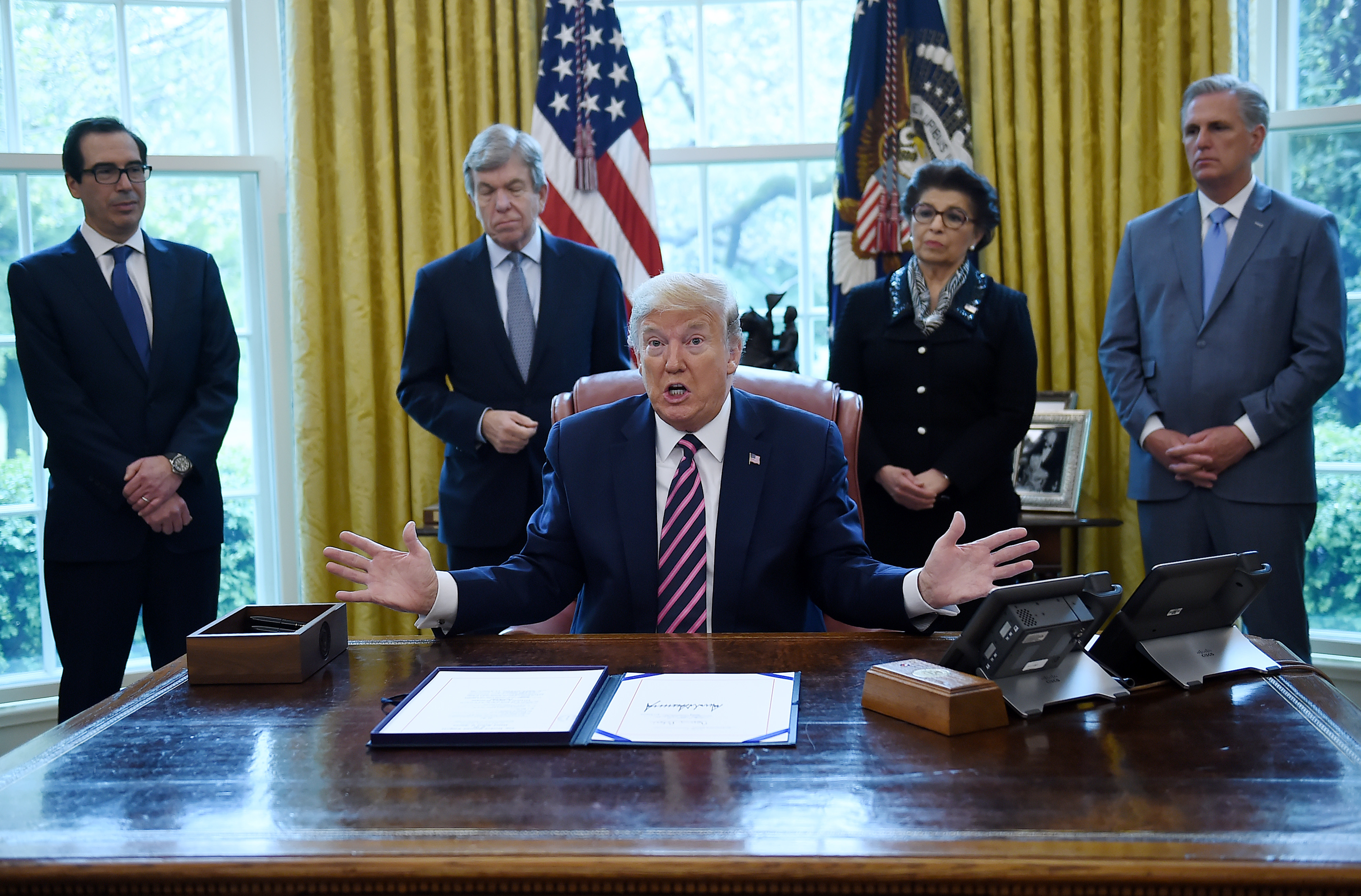 US President Donald Trump speaks after signing the Paycheck Protection Program and Health Care Enhancement Act in the Oval Office of the White House in Washington, DC, on April 24, 2020. With trump are (L-R) US Secretary of the Treasury Steve Mnuchin, US Republican Senator Roy Blunt of Missouri, Administrator of the Small Business Administration Jovita Carranza and House Minority Leader, Republican Representative Kevin McCarthy of California. - The $483 billion stimulus act will back small businesses on the brink of bankruptcy, and allocate more money for health-care providers and virus testing. (Photo by OLIVIER DOULIERY/AFP via Getty Images)