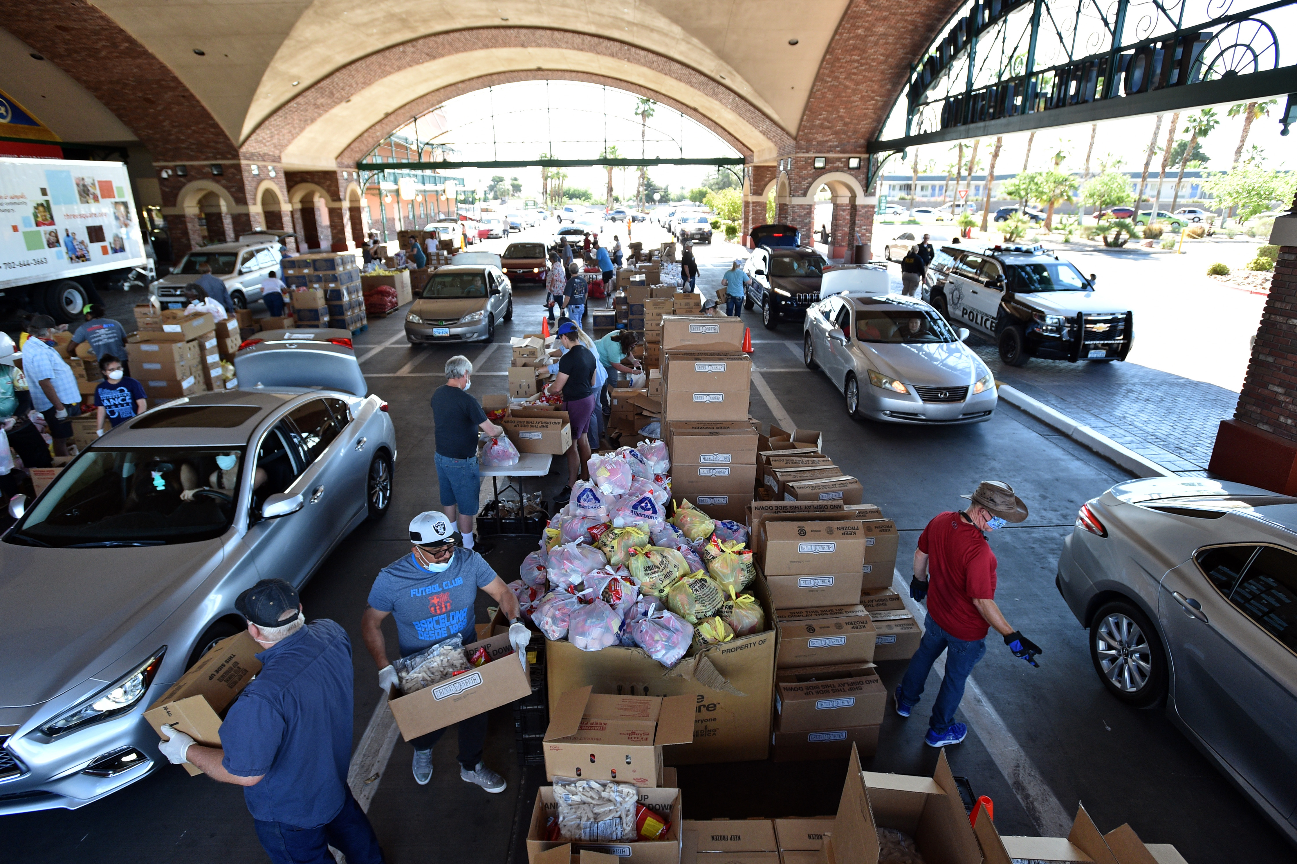 Volunteers give out groceries at a drive-thru Three Square Food Bank emergency food distribution site at Boulder Station Hotel & Casino in response to an increase in demand amid the coronavirus pandemic on April 29, 2020 in Las Vegas, Nevada. - Three Square is currently operating dozens of emergency distribution sites at various times and dates throughout Southern Nevada to assist a growing number of people, many recently unemployed. (Photo by David Becker / AFP) (Photo by DAVID BECKER/AFP via Getty Images)Volunteers give out groceries at a drive-thru Three Square Food Bank emergency food distribution site at Boulder Station Hotel & Casino in response to an increase in demand amid the coronavirus pandemic on April 29, 2020 in Las Vegas, Nevada. - Three Square is currently operating dozens of emergency distribution sites at various times and dates throughout Southern Nevada to assist a growing number of people, many recently unemployed. (Photo by DAVID BECKER/AFP via Getty Images)