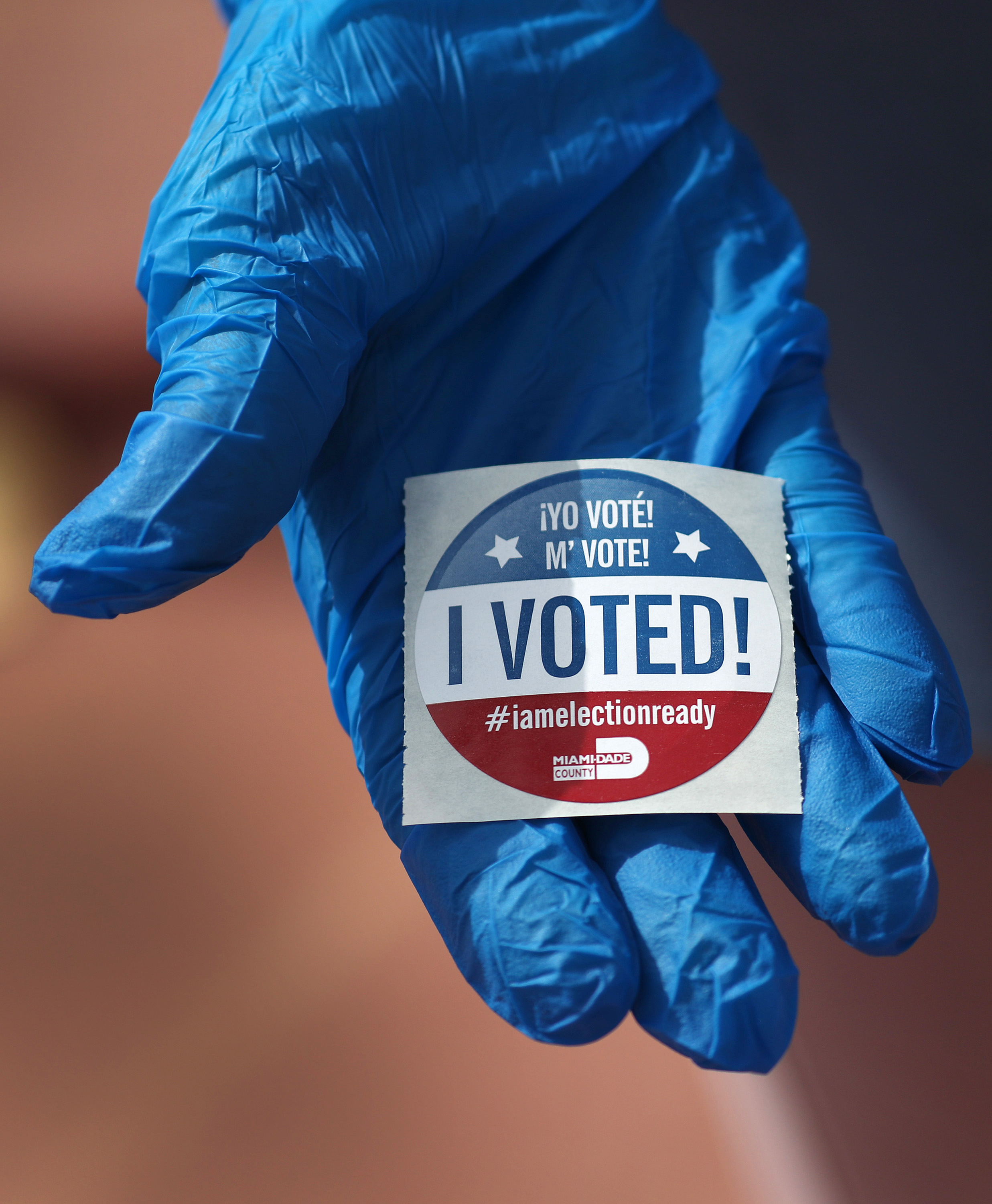 A voter holds an, 'I Voted!', sticker. (Photo by Joe Raedle/Getty Images)