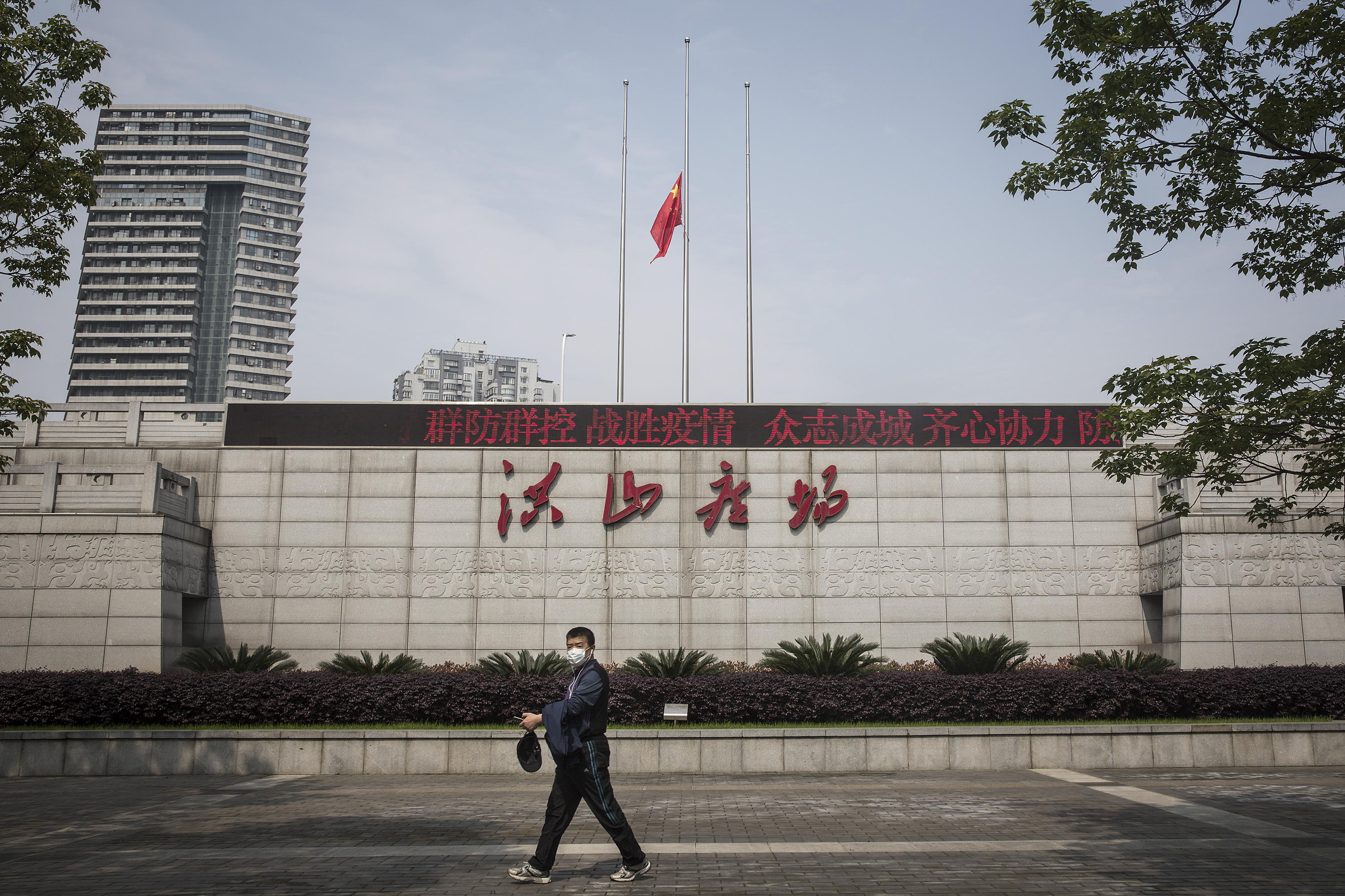 A resident passes in Hongshan square as Chinese national flag flies. (Photo by Getty Images)