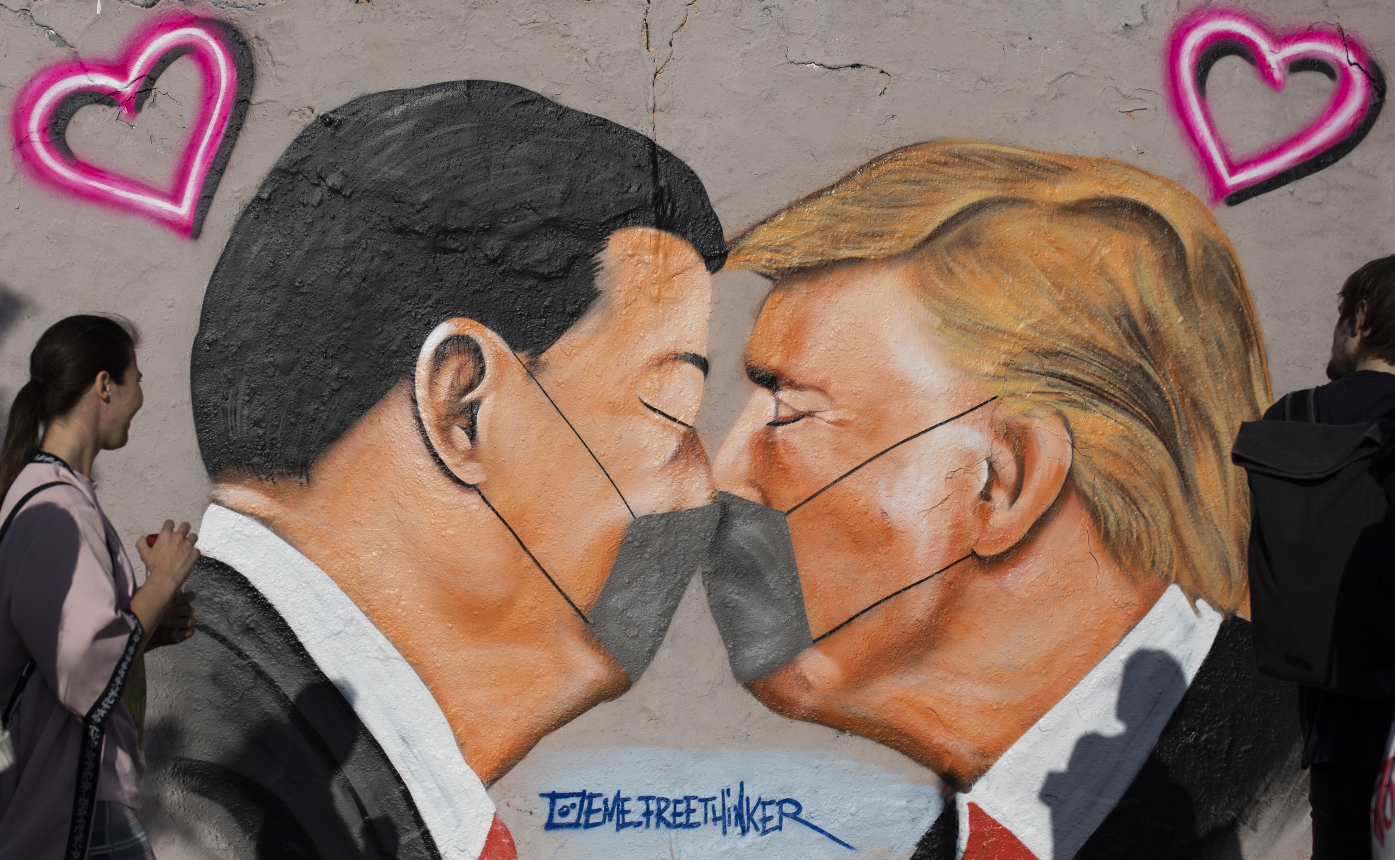 BERLIN, GERMANY - APRIL 26: Graffiti showing US President Donald Trump and Chinese President Xi Jinping, wearing protective masks kissing is seen during the novel coronavirus crisis on April 26, 2020 in Berlin, Germany. Germany is taking its first steps to ease restrictions on public life that had been imposed weeks ago in order to stem the spread of the coronavirus. Shops across the country are reopening, factory assembly lines are restarting and high schools are holding final exams. Health leaders are monitoring the process carefully for any resurgence of coronavirus infections. The number of infections nationwide is still rising, though so far at a declining rate. (Photo by Maja Hitij/Getty Images)