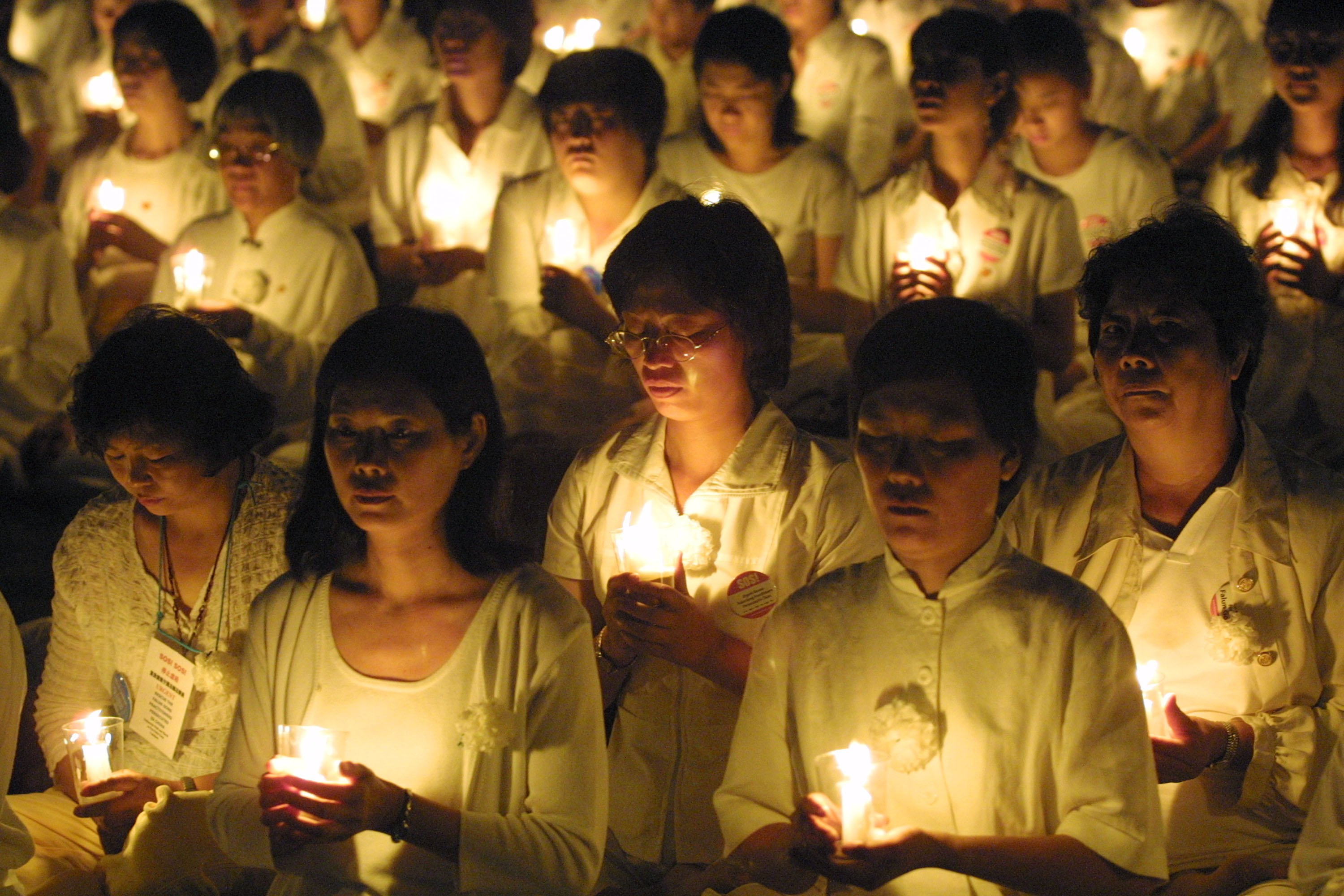 Members of the Falun Gong spiritual movement hold candles during a candlelight vigil July 19, 2001 in Washington, DC to mark the second anniversary of a Chinese government crackdown on the outlawed religious sect. (Photo by Alex Wong/Getty Images)