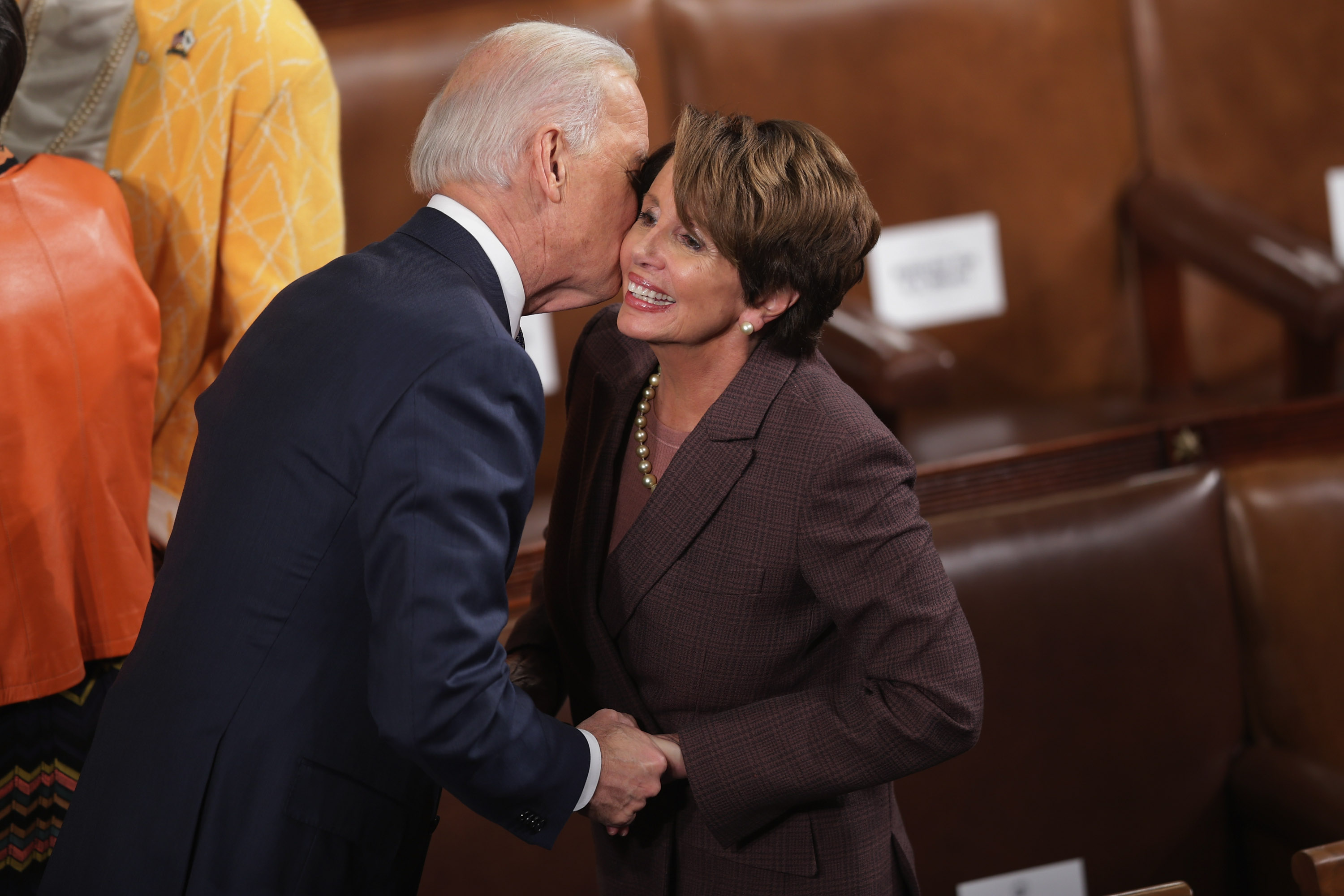 WASHINGTON, DC - JANUARY 28: Vice President Joe Biden (L) kisses House Minority Leader Nancy Pelosi (D-CA) before U.S. President Barack Obama delivers the State of the Union address to a joint session of Congress in the House Chamber at the U.S. Capitol on January 28, 2014 in Washington, DC. In his fifth State of the Union address, Obama is expected to emphasize on healthcare, economic fairness and new initiatives designed to stimulate the U.S. economy with bipartisan cooperation. (Photo by Chip Somodevilla/Getty Images)