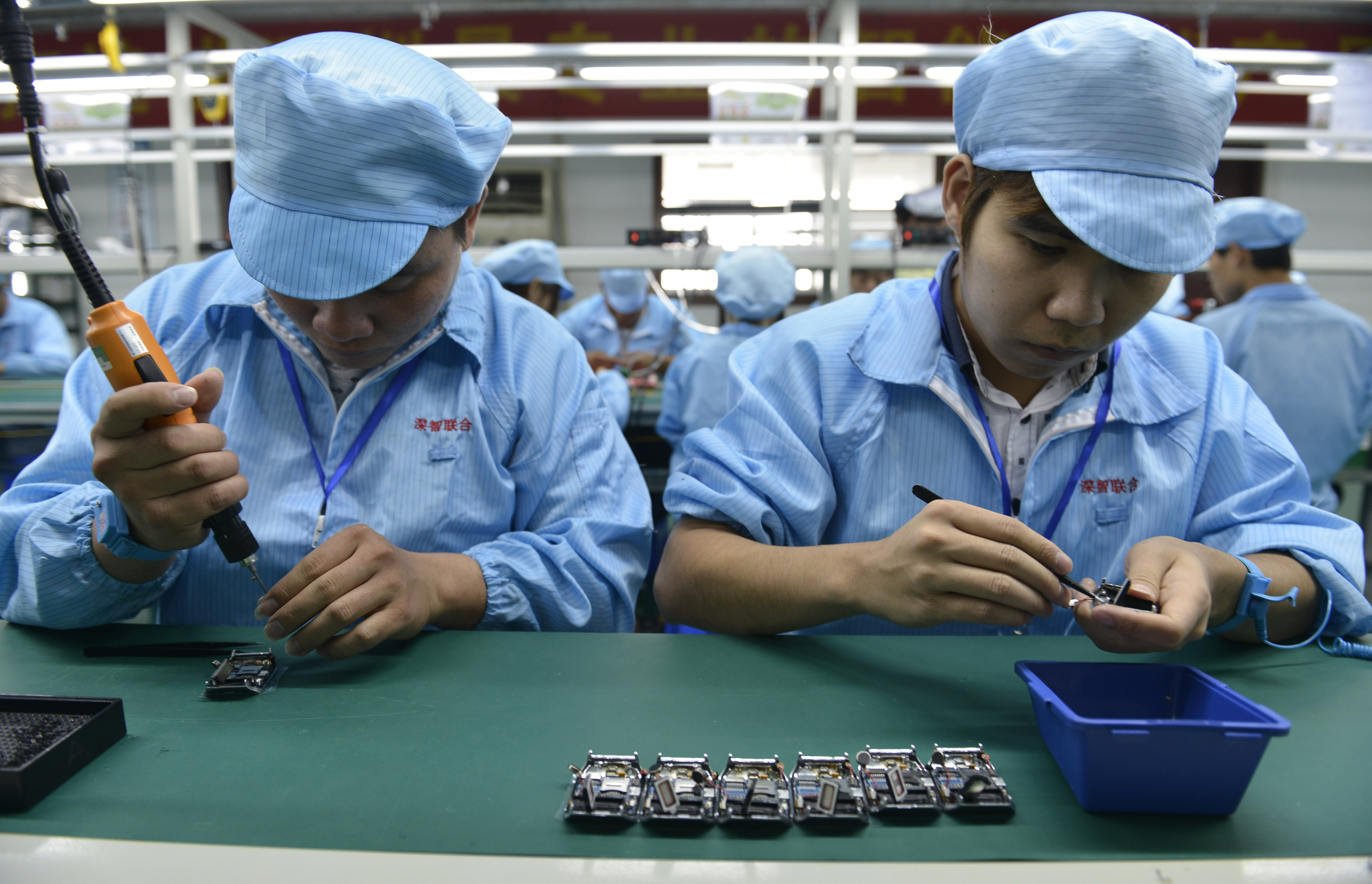 This picture taken on April 22, 2015 shows Chinese workers assembling a cheaper local alternative to the Apple Watch in a factory producing thousands every day in Shenzhen, in southern China's Guangdong province. (STR/AFP via Getty Images)