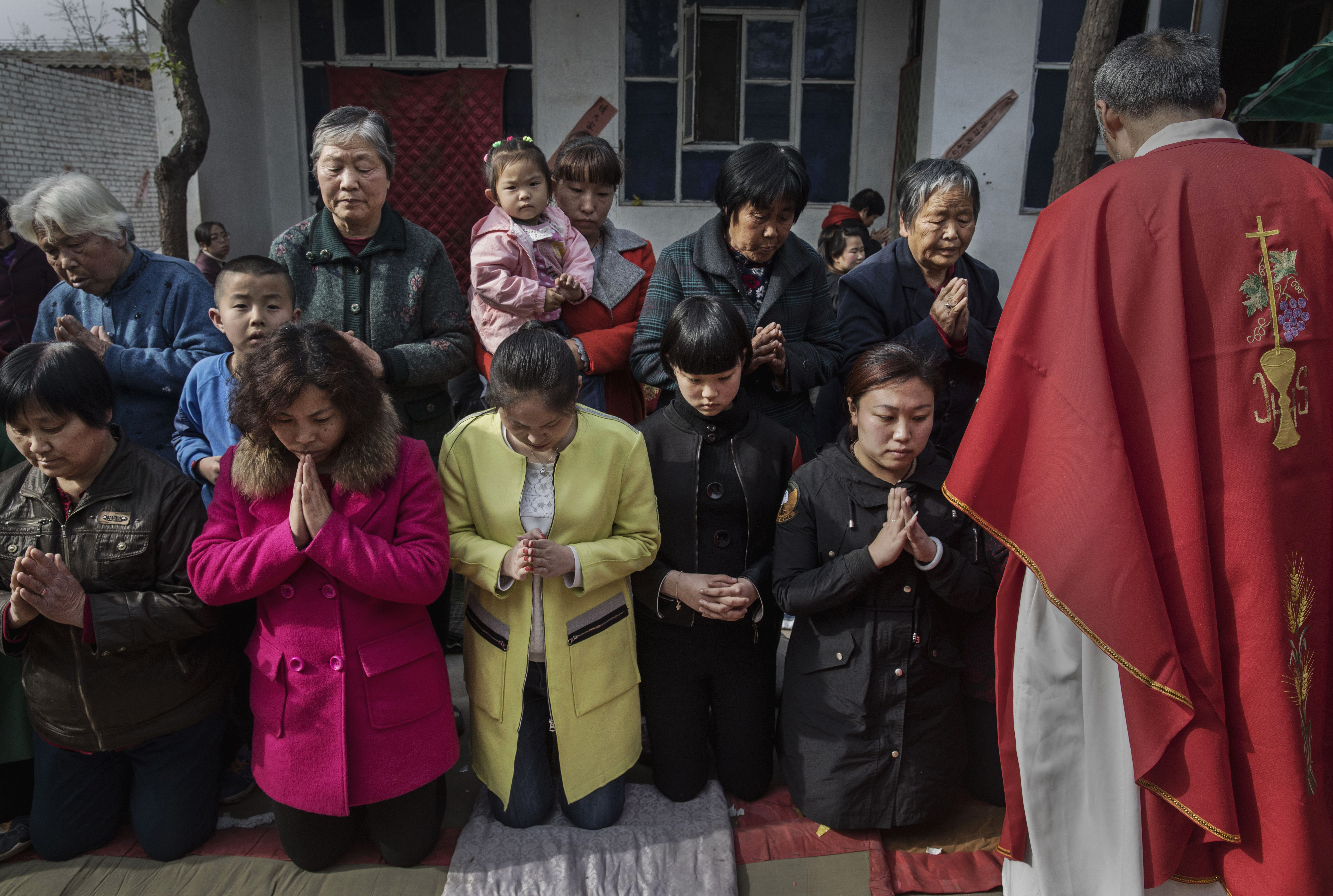 Chinese Catholic worshippers wait to take communion at the Palm Sunday Mass during the Easter Holy Week at an