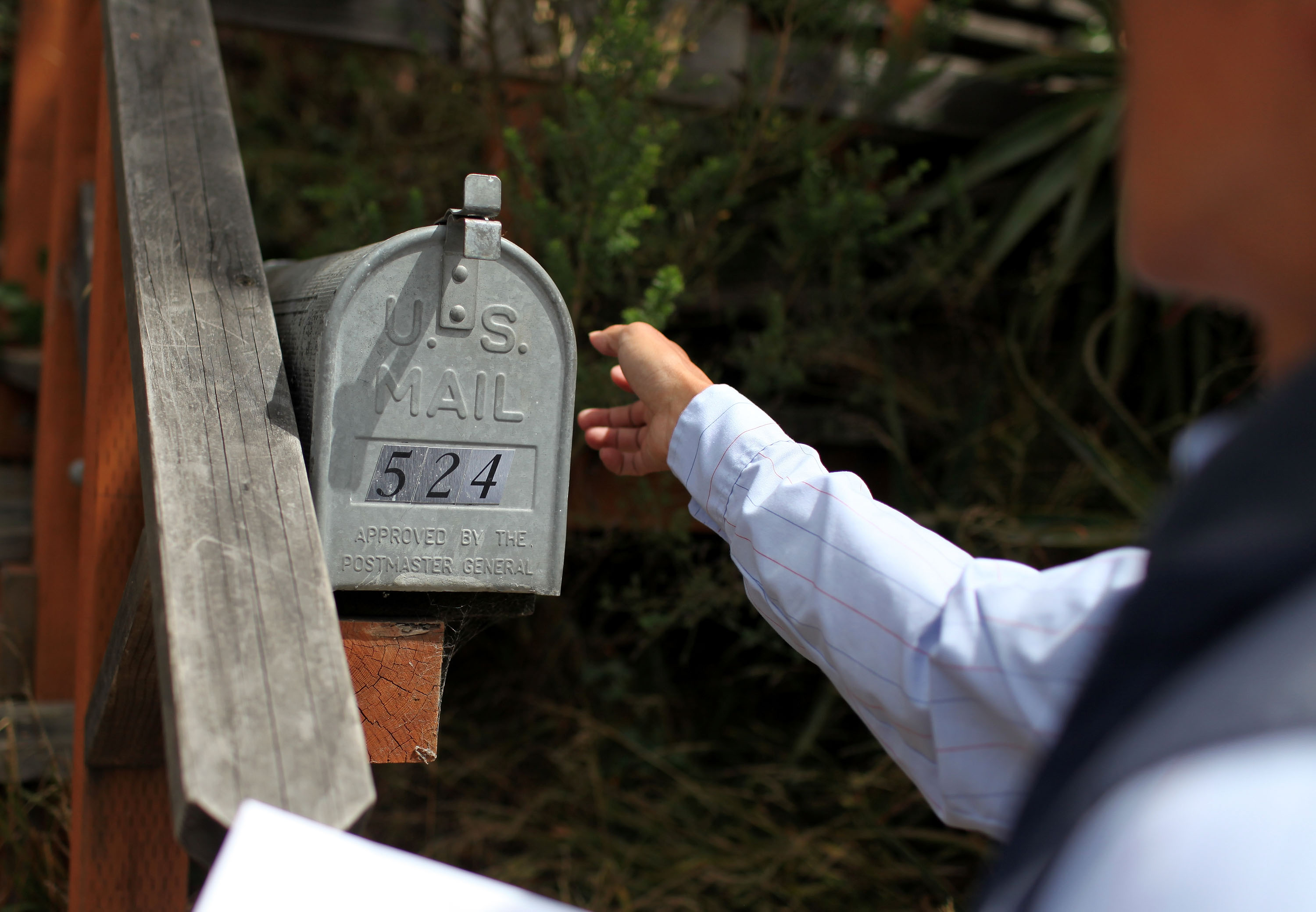 US Postal Service letter carrier Anthony Ow prepares to place letters in a mailbox. (Photo by Justin Sullivan/Getty Images)