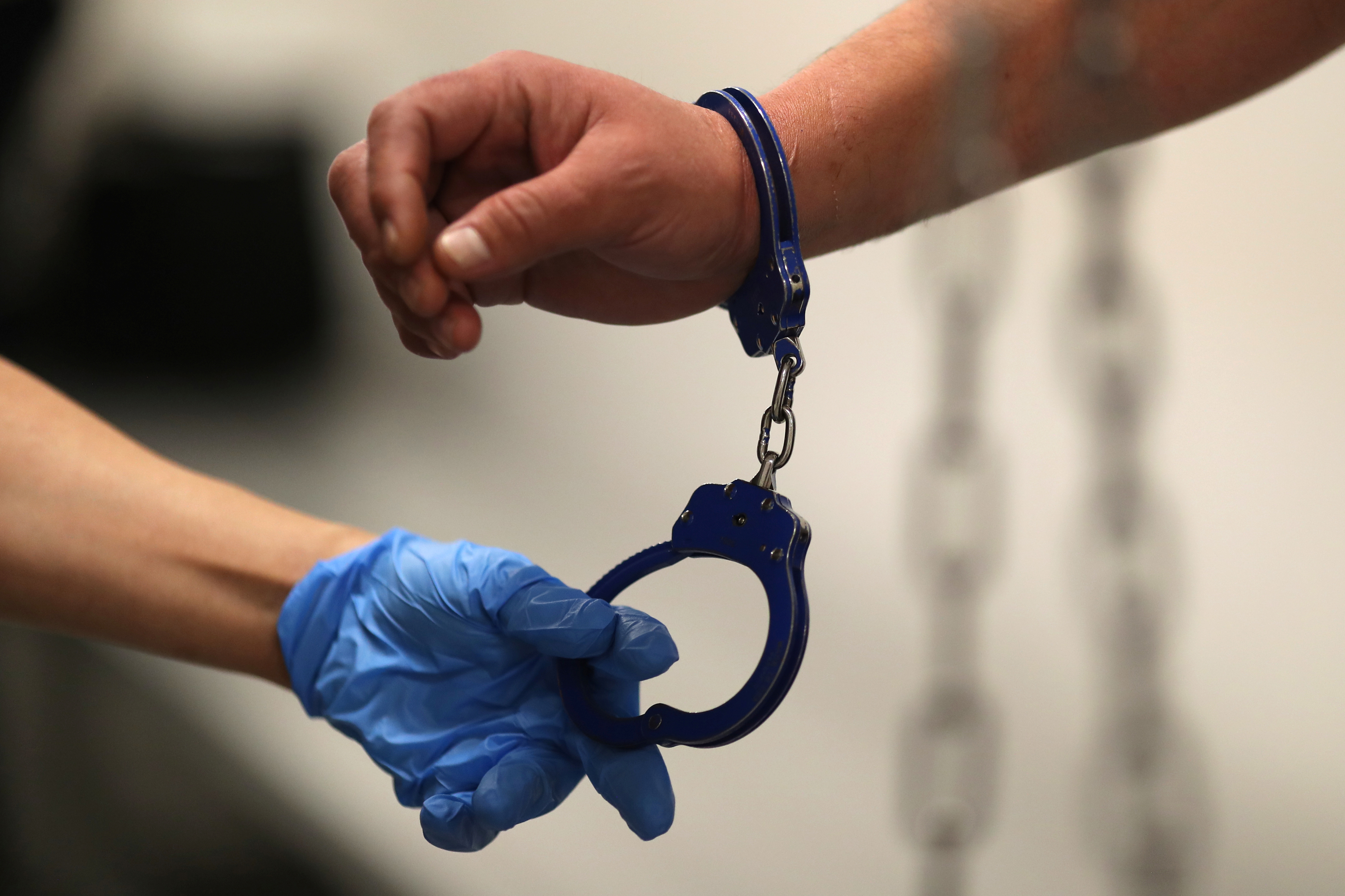 A U.S. Immigration and Customs Enforcement's (ICE) Fugitive Operations Agent takes handcuffs off before booking an immigrant in Los Angeles