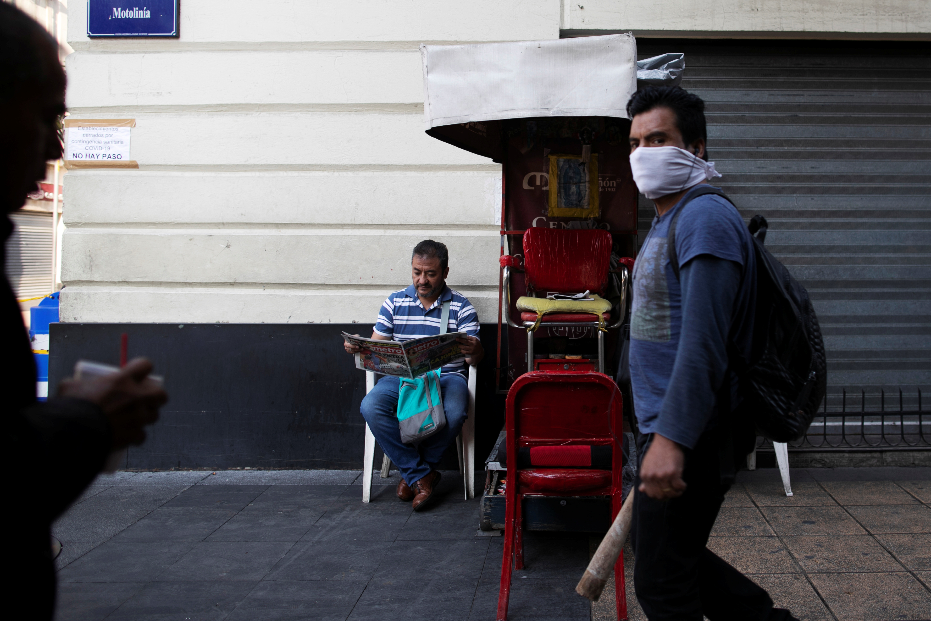 A shoe shiner reads the paper as he waits for costumers in one of the main streets in downtown as Mexico's government declared a health emergency and issued stricter rules to curb the spread of the coronavirus disease (COVID-19), in Mexico City