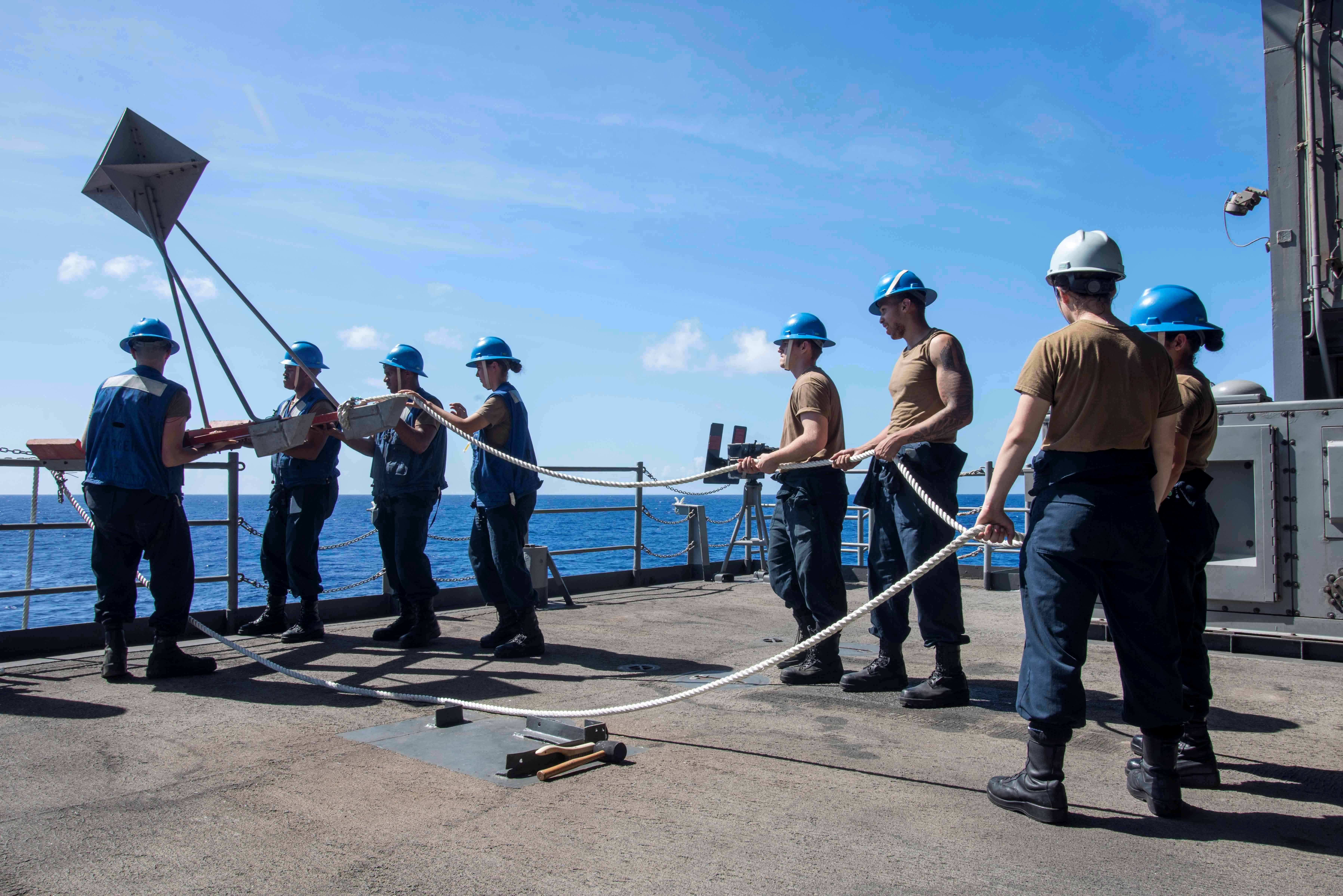 U.S. Navy sailors lower a larne target from the fantail of the aircraft carrier USS Theodore Roosevelt in the Philippine Sea March 21, 2020. (U.S. Navy/Mass Communication Specialist 3rd Class Dartanon D. Delagarza/Handout via REUTERS)
