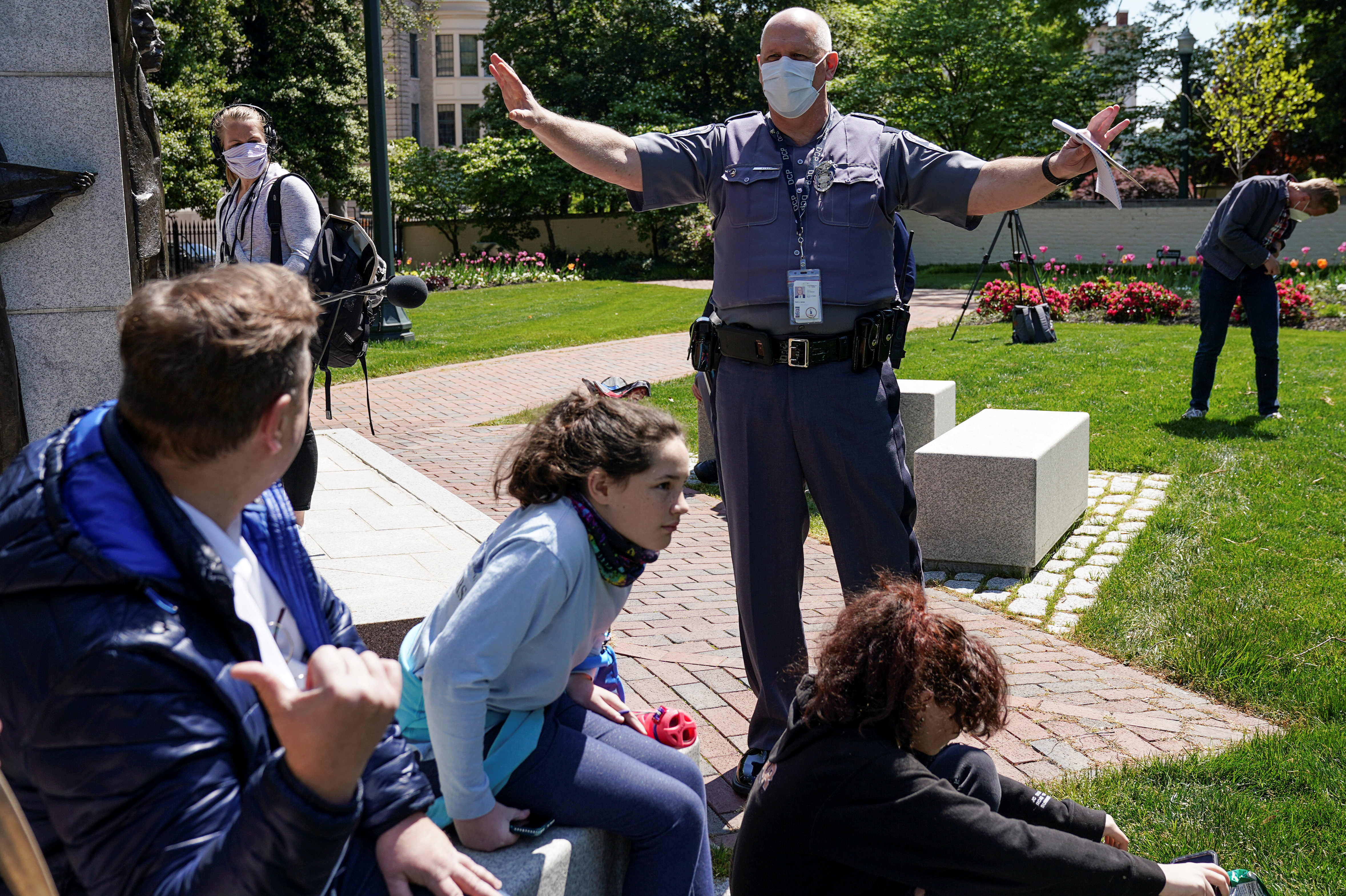 A police officer asks demonstrators to spread out as they gather in opposition to Virginia's stay-at-home order and business closures in the wake of the coronavirus disease (COVID-19) outbreak, during a protest against the lockdown measures in Richmond, Virginia, U.S., Apr. 16, 2020. REUTERS/Kevin Lamarque