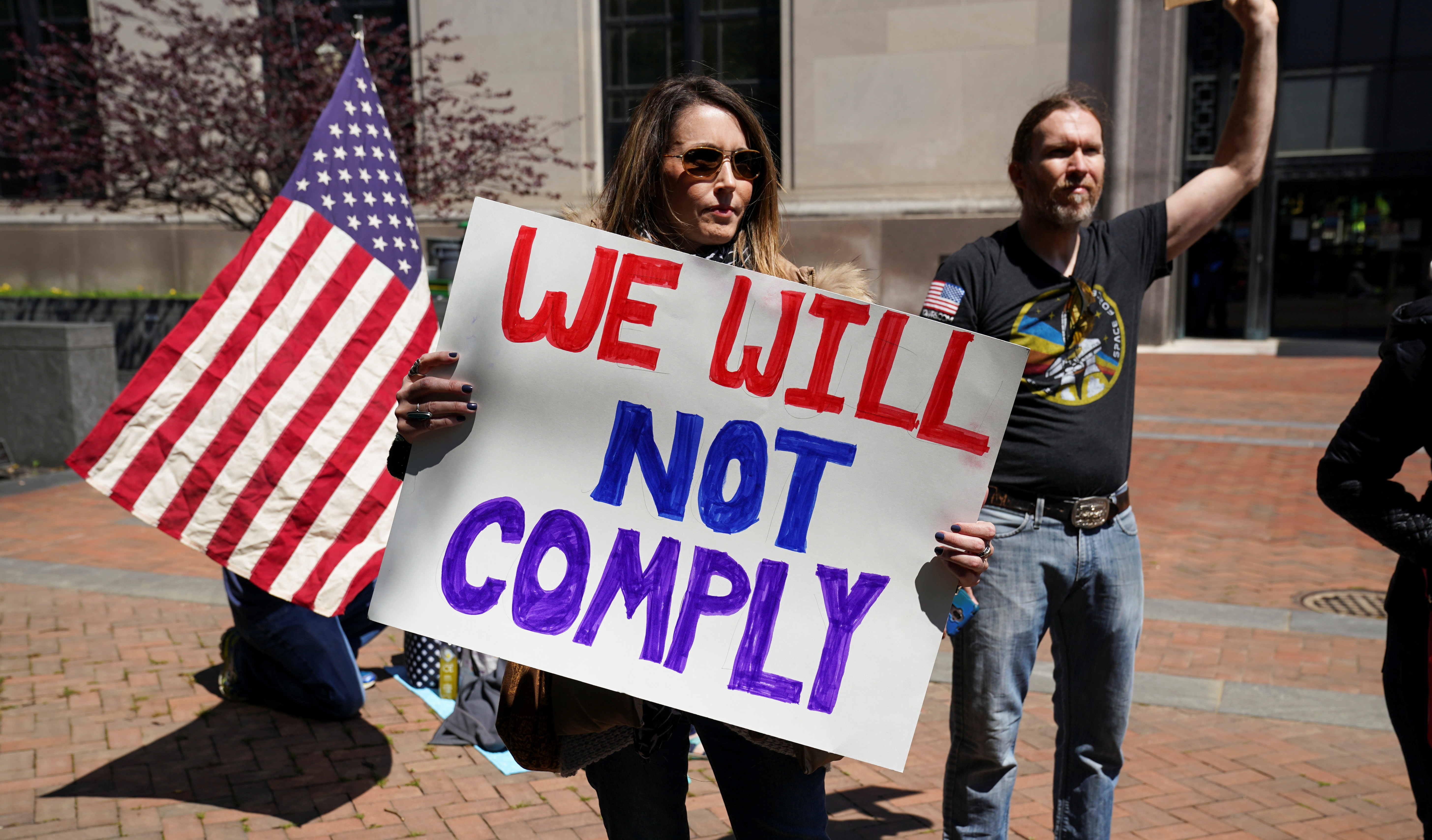 "A protestor carries a sign reading ""We Will Not Comply"" during a demonstration outside the Virginia State Capitol to protest Virginia's stay-at-home order and business closures in the wake of the coronavirus disease (COVID-19) outbreak in Richmond, Virginia, U.S., Apr. 16, 2020. REUTERS/Kevin Lamarque"