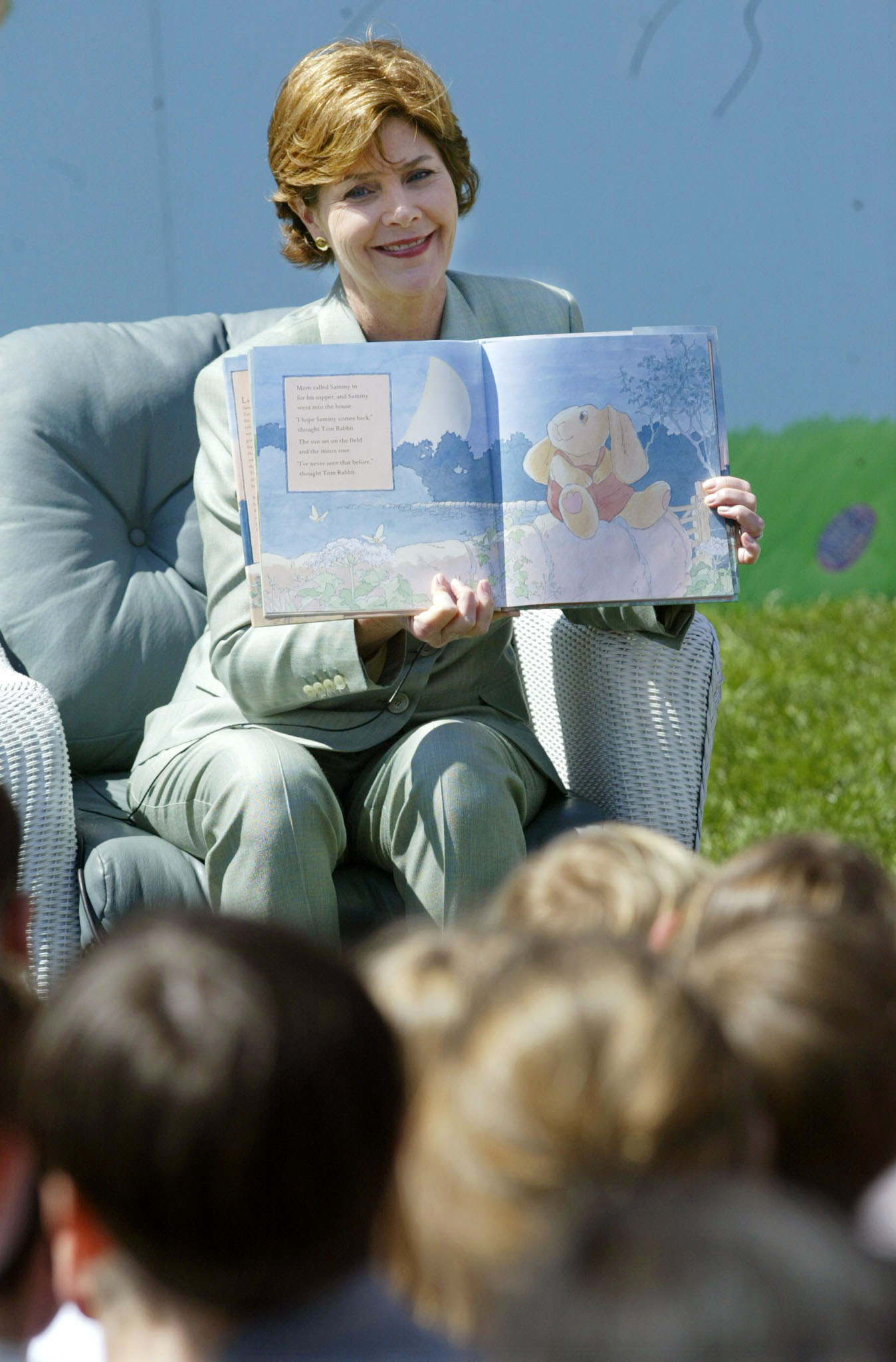 "First lady Laura Bush reads ""Tom Rabbit"" to children attending the Easter Egg Roll at the White House, April 1, 2002. REUTERS/Kevin Lamarque"