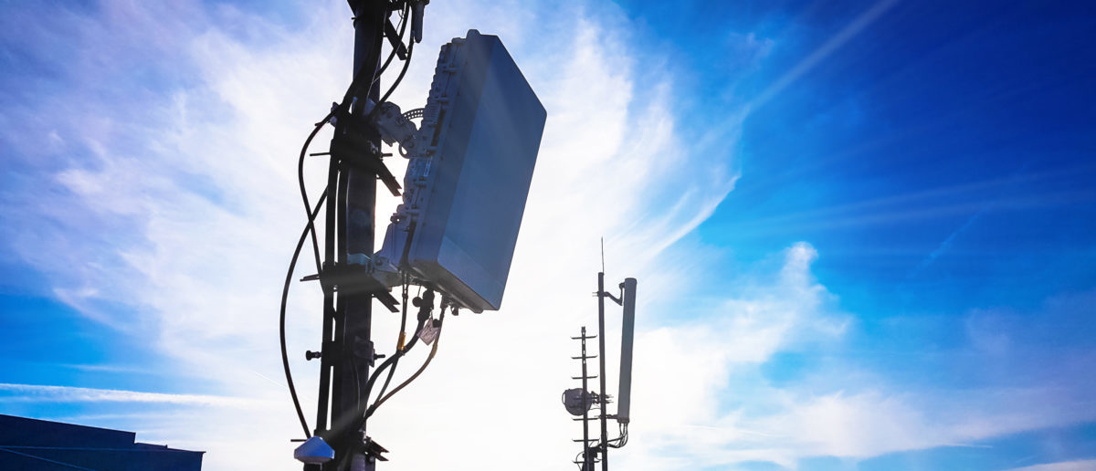 Silhouette of 5G smart cellular network antenna base station on the telecommunication mast. Shutterstock/TPROduction