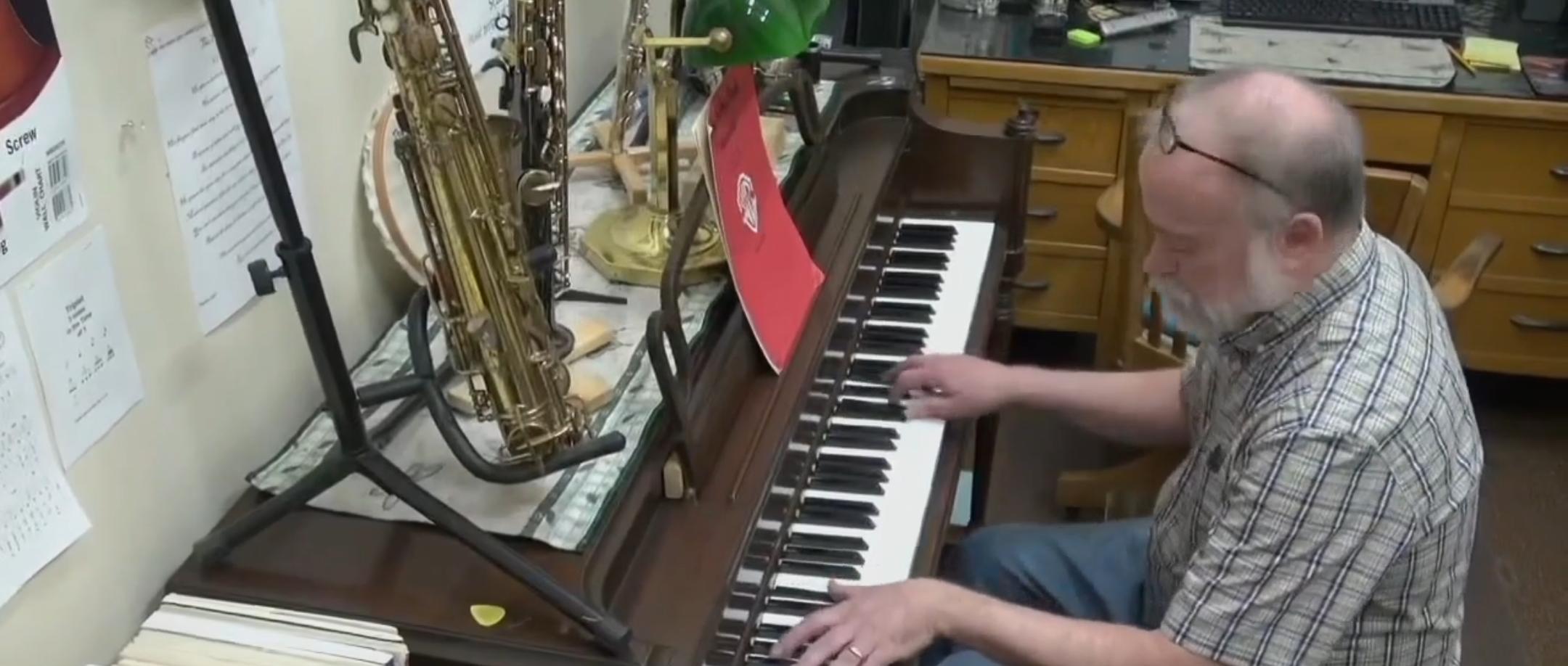 Steve Walker playing piano in his store. (Screenshot/FOX 17)