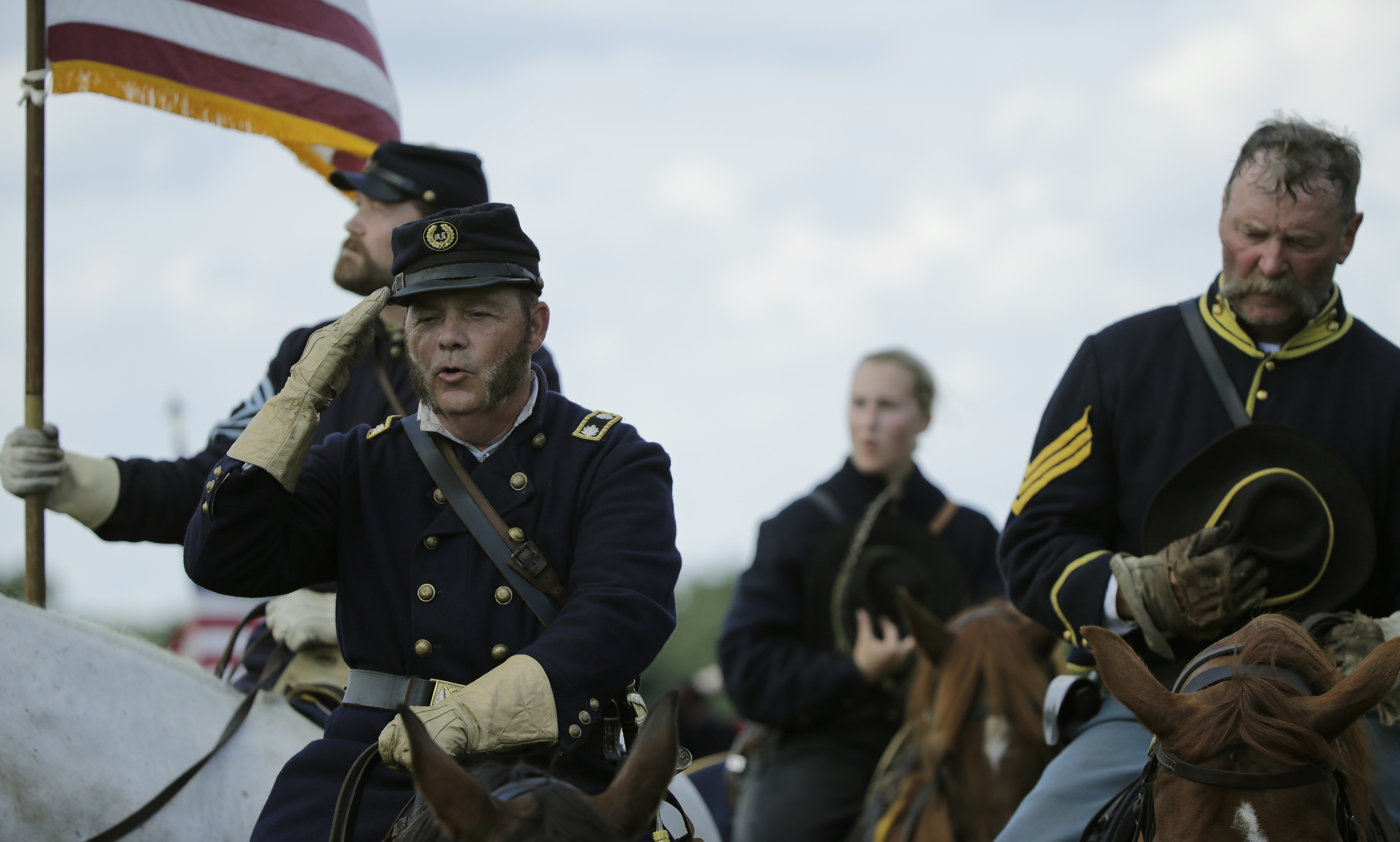 """Federal (Union) officers listen to the national anthem before the final battle of the Gettysburg conflict, """"Pickett's Charge,"""" between Confederate and Federal (Union) soldiers as part of re-enactment activities July 7, 2013, recognizing the 150th anniversary of the U.S. Civil War battle in Gettysburg, Pennsylvania. Gettysburg officials are expecting 250,000 visitors to visit the small south-central Pennsylvania borough of about 7,700 residents for the anniversary. REUTERS/Gary Cameron"""