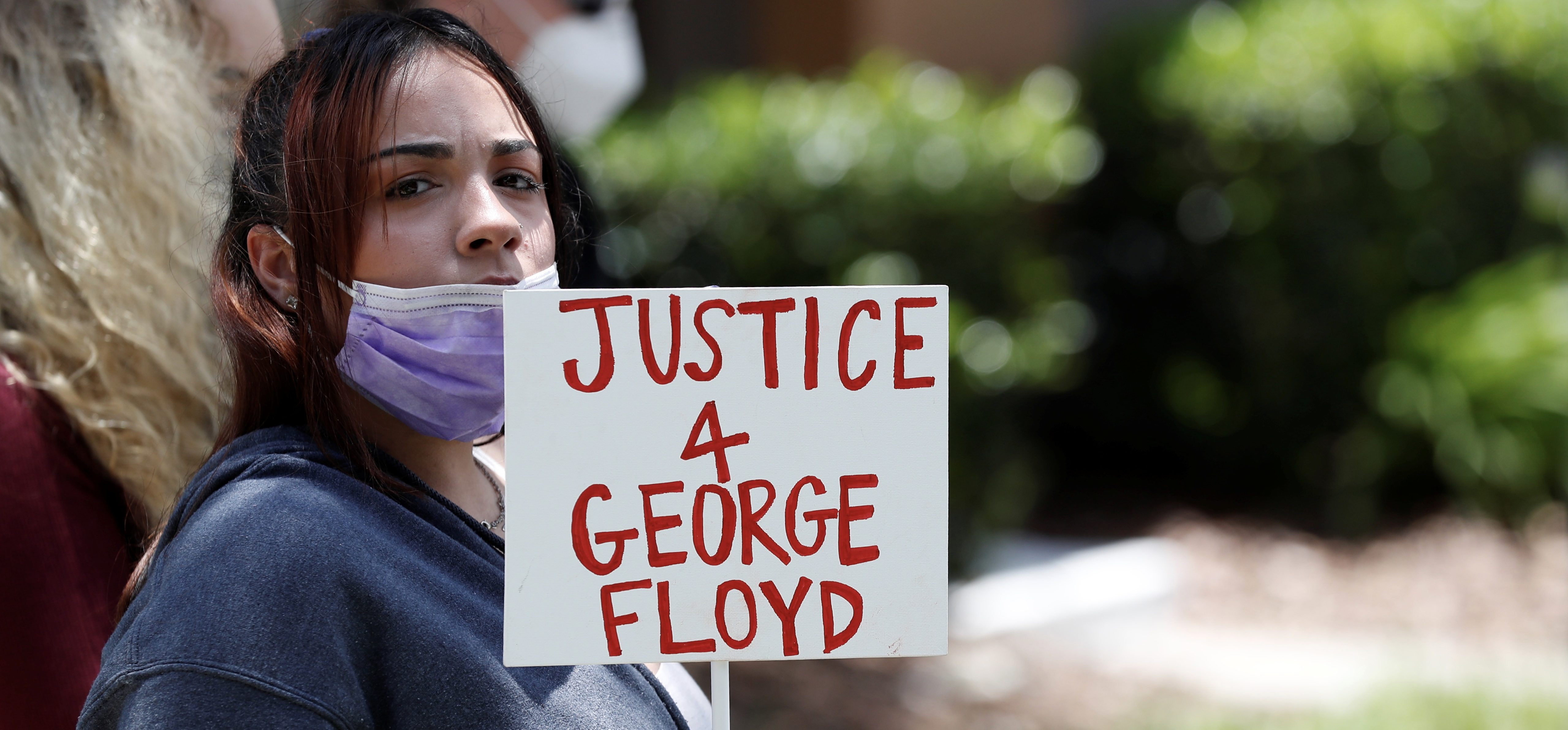 A protester holds a sign outside the Florida home of former Minneapolis police officer Derek Chauvin, who was recorded with his knee on the neck of African-American man George Floyd before his death, in the Windermere neighbourhood of Orlando, Florida, U.S. May 29, 2020. REUTERS/Scott Audette