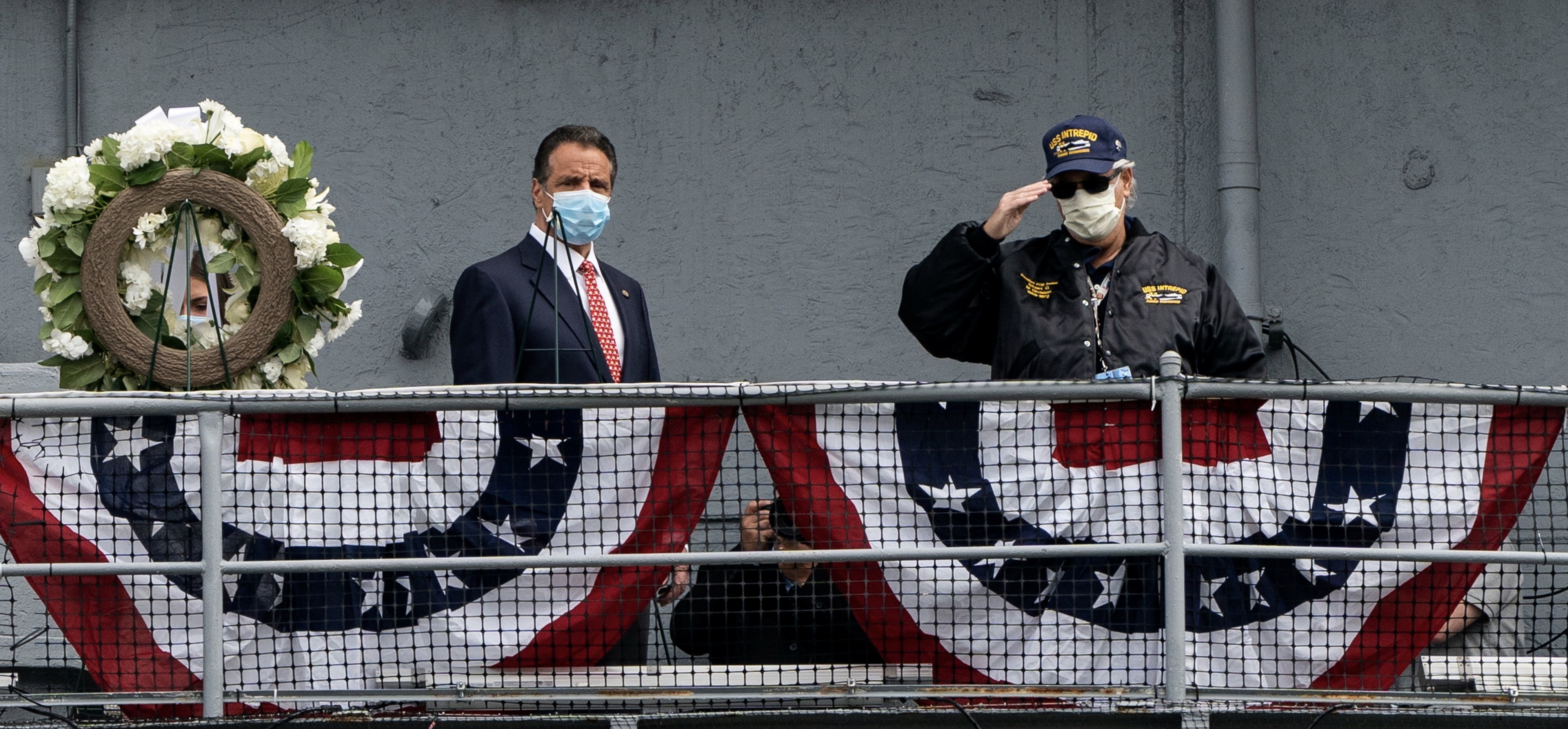 President of the Intrepid Former Crew members Association Stuart Gelband (r) wearing a protective mask salutes next to New York Governor Andrew Cuomo during the Memorial day ceremony at the Intrepid Sea, Air & Space Museum following the outbreak of the coronavirus disease (COVID-19) in New York, U.S., May 25, 2020.. REUTERS/Jeenah Moon
