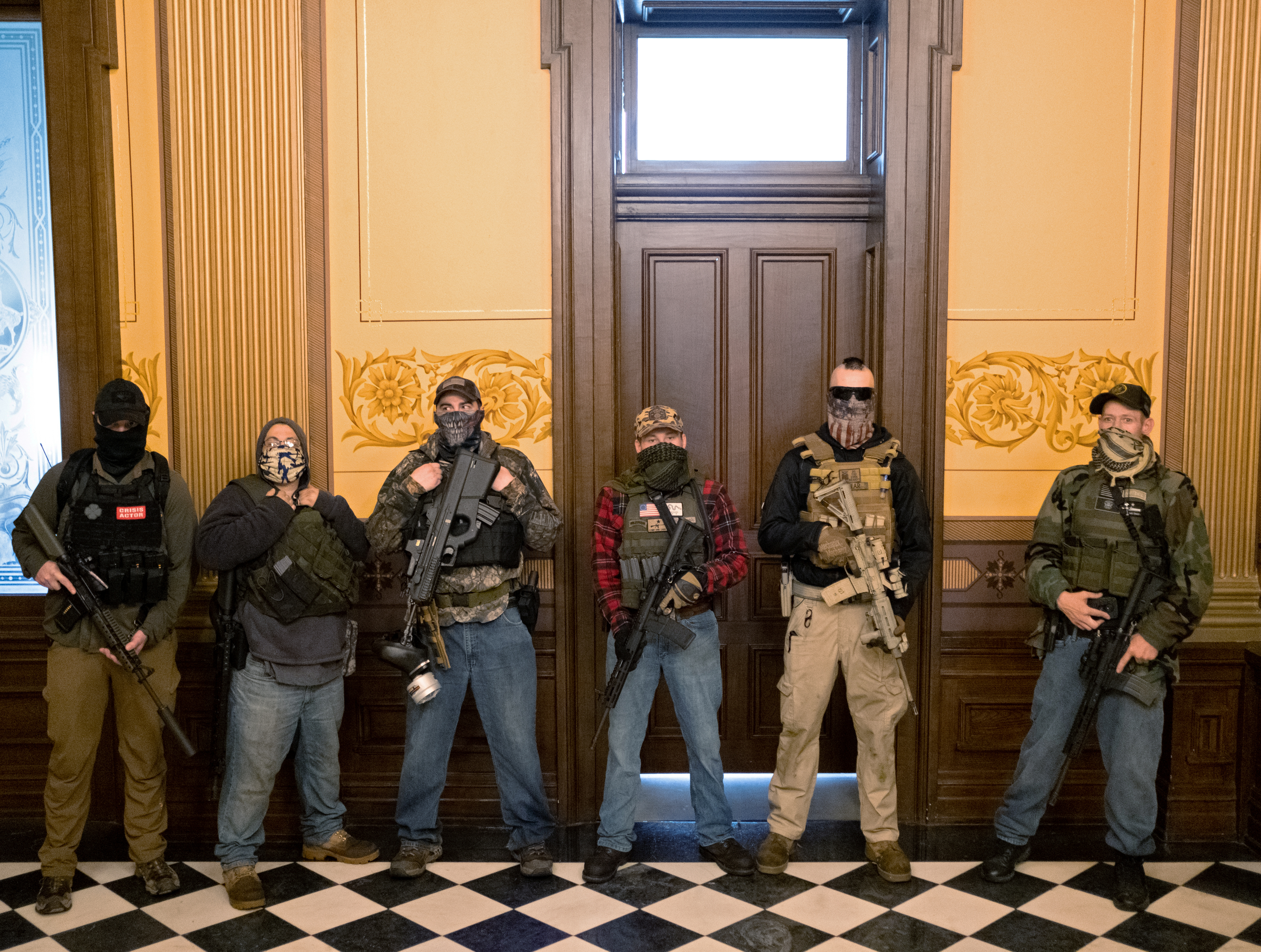A militia group with no political affiliation from Michigan stands in front of the Governors office after protesters occupied the state capitol building during a vote to approve the extension of Governor Gretchen Whitmer's emergency declaration/stay-at-home order due to the coronavirus disease (COVID-19) outbreak, at the state capitol in Lansing, Michigan, U.S. Apr. 30, 2020. REUTERS/Seth Herald