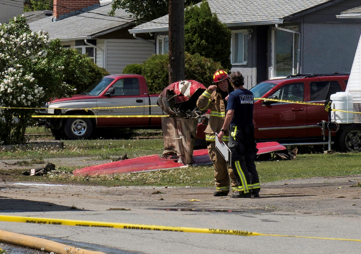 Fire officials talk in a residential neighbourhood street in front of the tail wreckage from a Royal Canadian Air Force Snowbirds jet after a member of the exhibition team crashed shortly after takeoff in Kamloops, British Columbia, Canada May 17, 2020. REUTERS/Dennis Owen