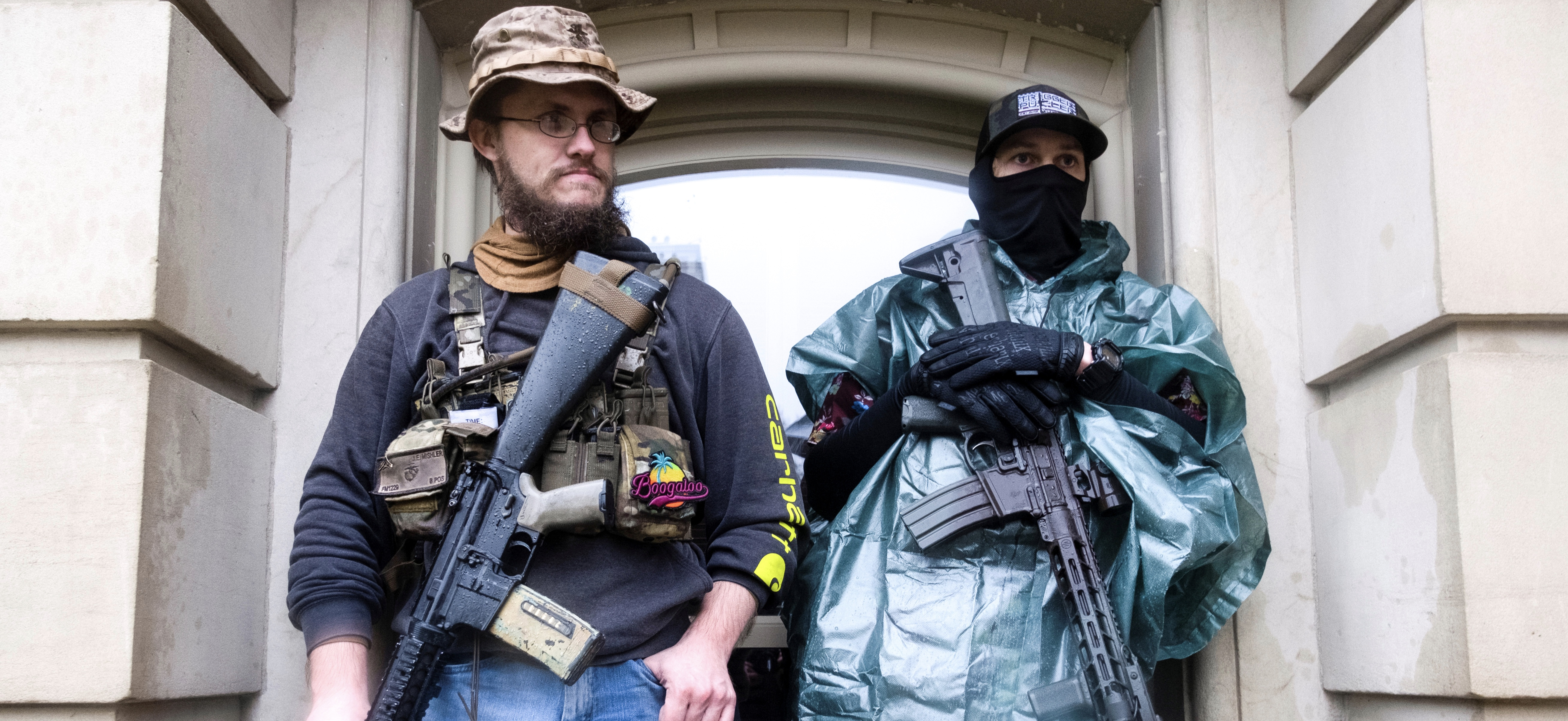 Protesters with long guns shelter from the heavy rain during a protest against Governor Gretchen Whitmer's extended stay-at-home orders intended to slow the spread of the coronavirus disease (COVID-19) at the Capitol building in Lansing, Michigan, U.S. May 14, 2020. REUTERS/Seth Herald