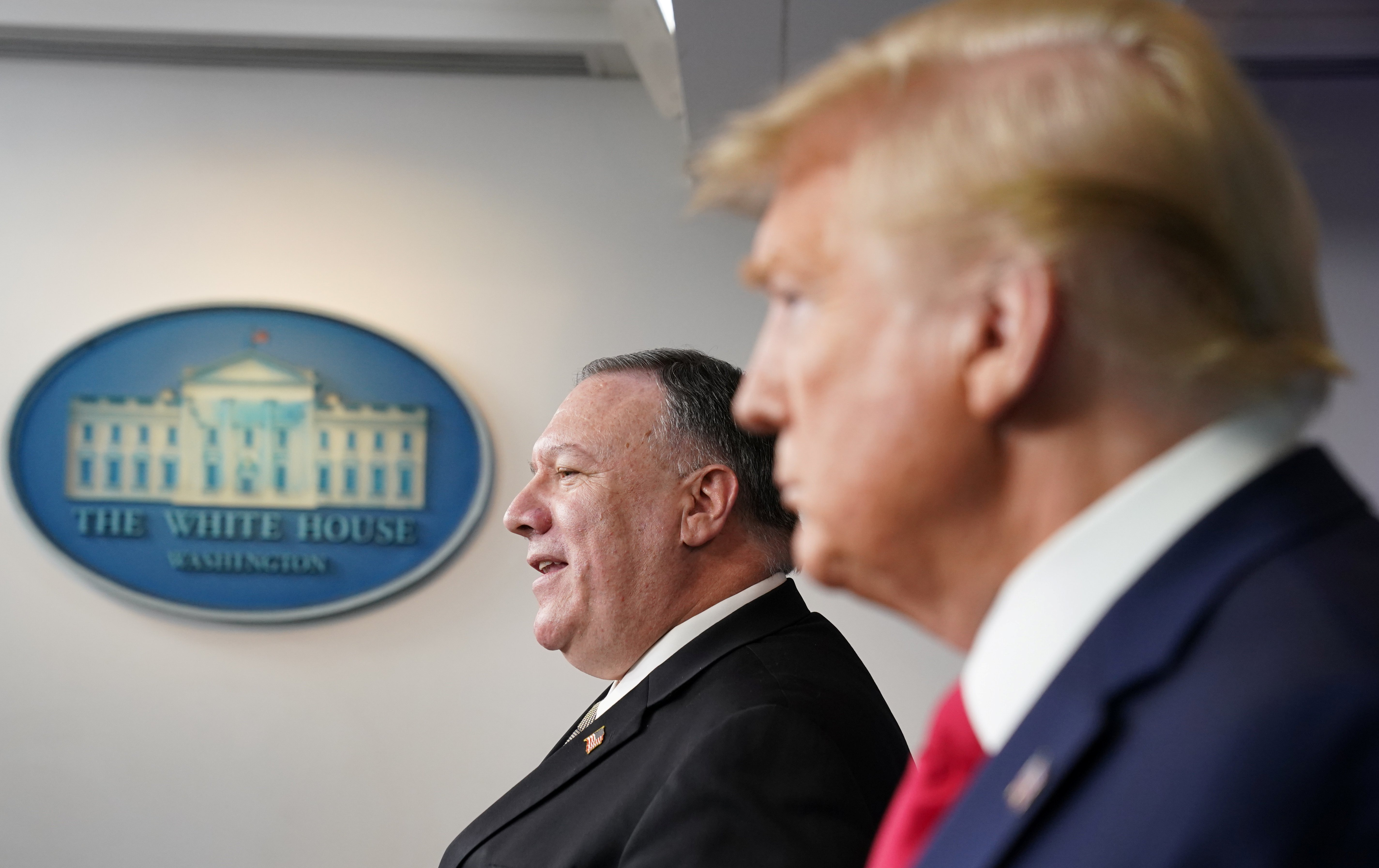 U.S. President Donald Trump listens as Secretary of State Mike Pompeo addresses the daily coronavirus task force briefing at the White House in Washington, U.S., Apr. 8, 2020. REUTERS/Kevin Lamarque