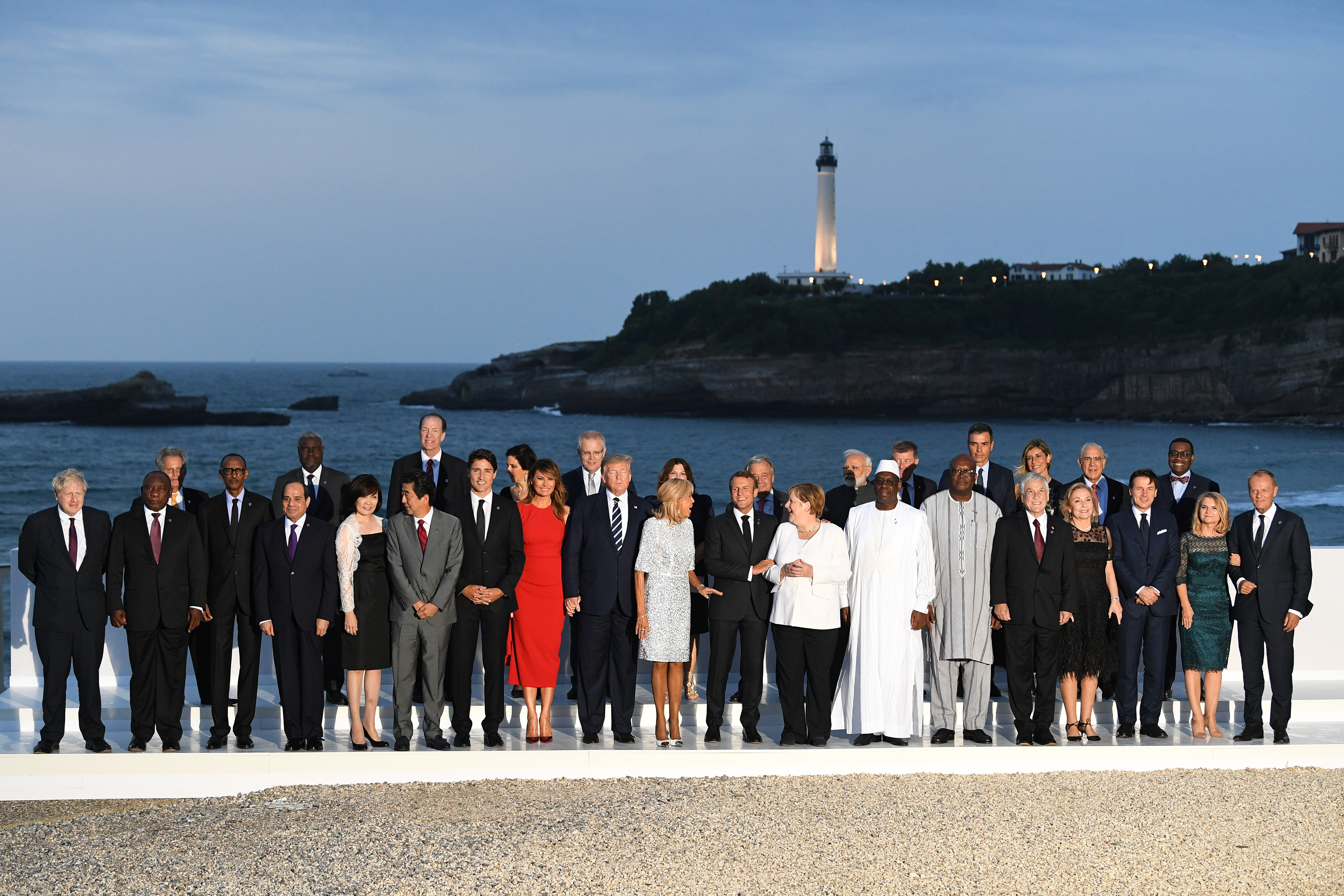 BIARRITZ, FRANCE - AUGUST 25: G7 leaders and guests pose for a family picture with the Biarritz lighthouse in the background on the second day of the annual G7 summit: (First row) L-R Britain's Prime Minister Boris Johnson, South Africa's President Cyril Ramaphosa, Rwanda's President Paul Kagame, African Union Chair Egyptian President Abdel Fattah el-Sisi, Japanese Prime Minister's wife Akie Abe, Japan's Prime Minister Shinzo Abe, Canada's Prime Minister Justin Trudeau, US First Lady Melania Trump, US President Donald Trump, French President's wife Brigitte Macron, France's President Emmanuel Macron, Germany's Chancellor Angela Merkel, Senegal's President Macky Sall, Burkina Faso's President Roch Marc Christian Kabore, Chile's President Sebastian Pinera, his wife Cecilia Morel, Italy's Prime Minister Giuseppe Conte, EU Council President's wife Malgorzata Tusk, European Council President Donald Tusk. (Second row) Chairperson of the African Union Commission Moussa Faki Mahamat (2nd,L), Australian Prime Minister Scott Morrison (5th, L) his wife Jenny Morrison, United Nations Secretary-General Antonio Guterres (7th,R), India's Prime Minister Narendra Modi (6th,R), Spain's Prime Minister Pedro Sanchez (4th,R), Spanish Prime Minister's wife Begona Sanchez (3rd,R), OECD Secretary-General Jose Angel Gurria (2nd,R), African Development Bank president Akinwumi Adesina (R) on August 25, 2019 in Biarritz, France. (Photo by Andrew Parsons/Getty Images)