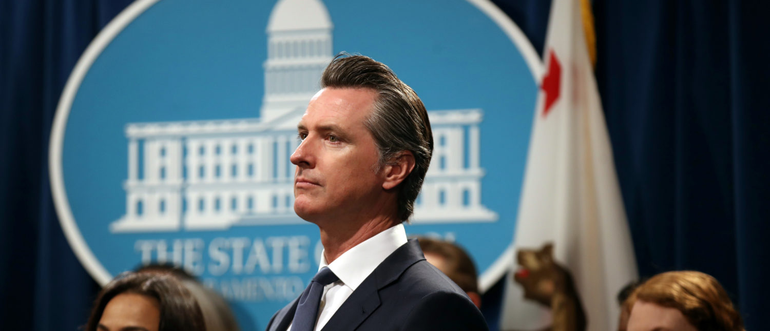 """SACRAMENTO, CALIFORNIA - AUGUST 16: California Gov. Gavin Newsom looks on during a news conference with California attorney General Xavier Becerra at the California State Capitol on August 16, 2019 in Sacramento, California. California attorney genera Xavier Becerra and California Gov. Gavin Newsom announced that the State of California is suing the Trump administration challenging the legality of a new """"public charge"""" rule that would make it difficult for immigrants to obtain green cards who receive public assistance like food stamps and Medicaid. (Photo by Justin Sullivan/Getty Images)"""
