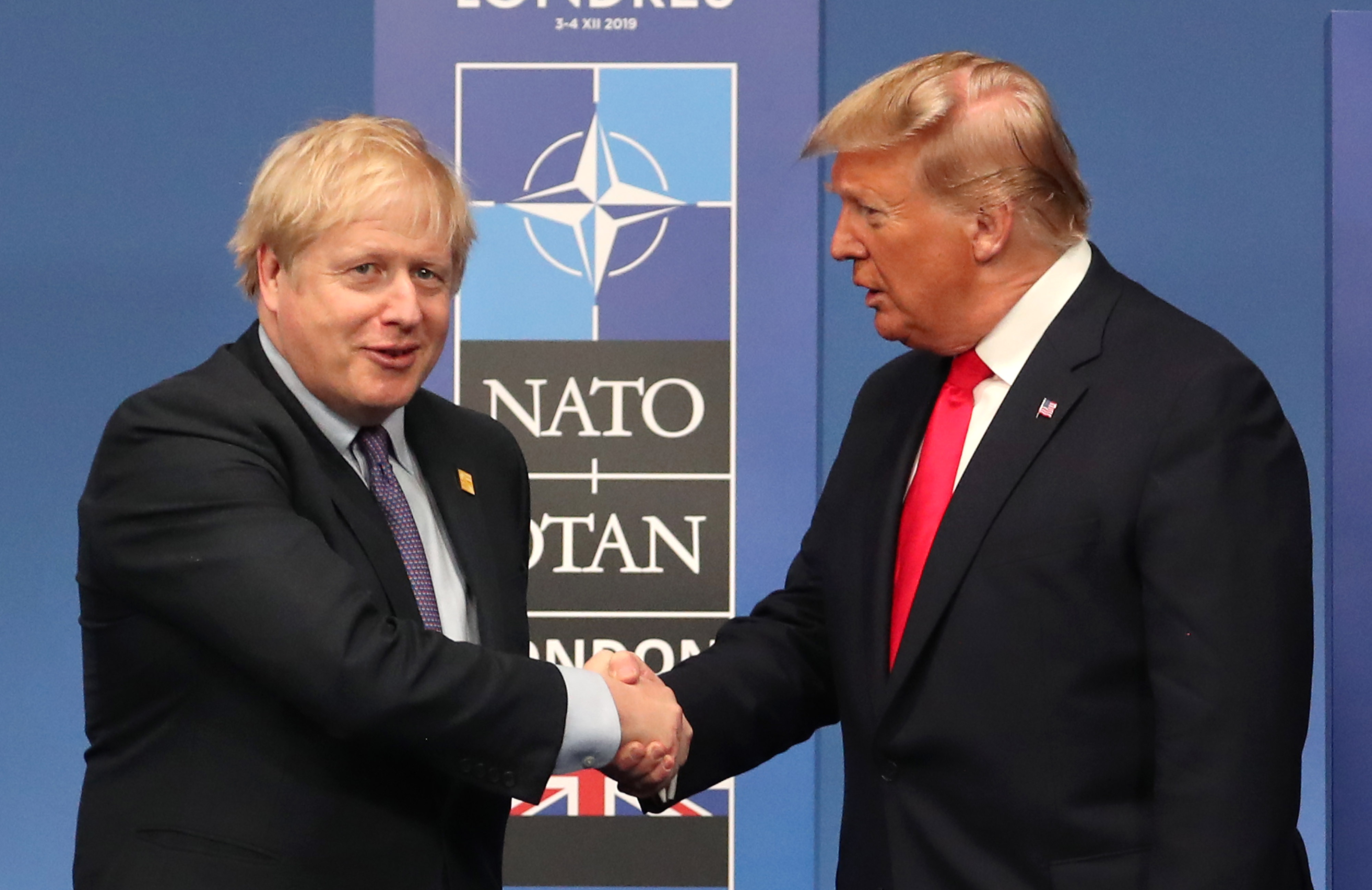 HERTFORD, ENGLAND - DECEMBER 04: British Prime Minister Boris Johnson shakes hands with US President Donald Trump onstage during the annual NATO heads of government summit on December 4, 2019 in Watford, England. France and the UK signed the Treaty of Dunkirk in 1947 in the aftermath of WW2 cementing a mutual alliance in the event of an attack by Germany or the Soviet Union. The Benelux countries joined the Treaty and in April 1949 expanded further to include North America and Canada followed by Portugal, Italy, Norway, Denmark and Iceland. This new military alliance became the North Atlantic Treaty Organisation (NATO). The organisation grew with Greece and Turkey becoming members and a re-armed West Germany was permitted in 1955. This encouraged the creation of the Soviet-led Warsaw Pact delineating the two sides of the Cold War. This year marks the 70th anniversary of NATO. (Photo by Steve Parsons-WPA Pool/Getty Images)
