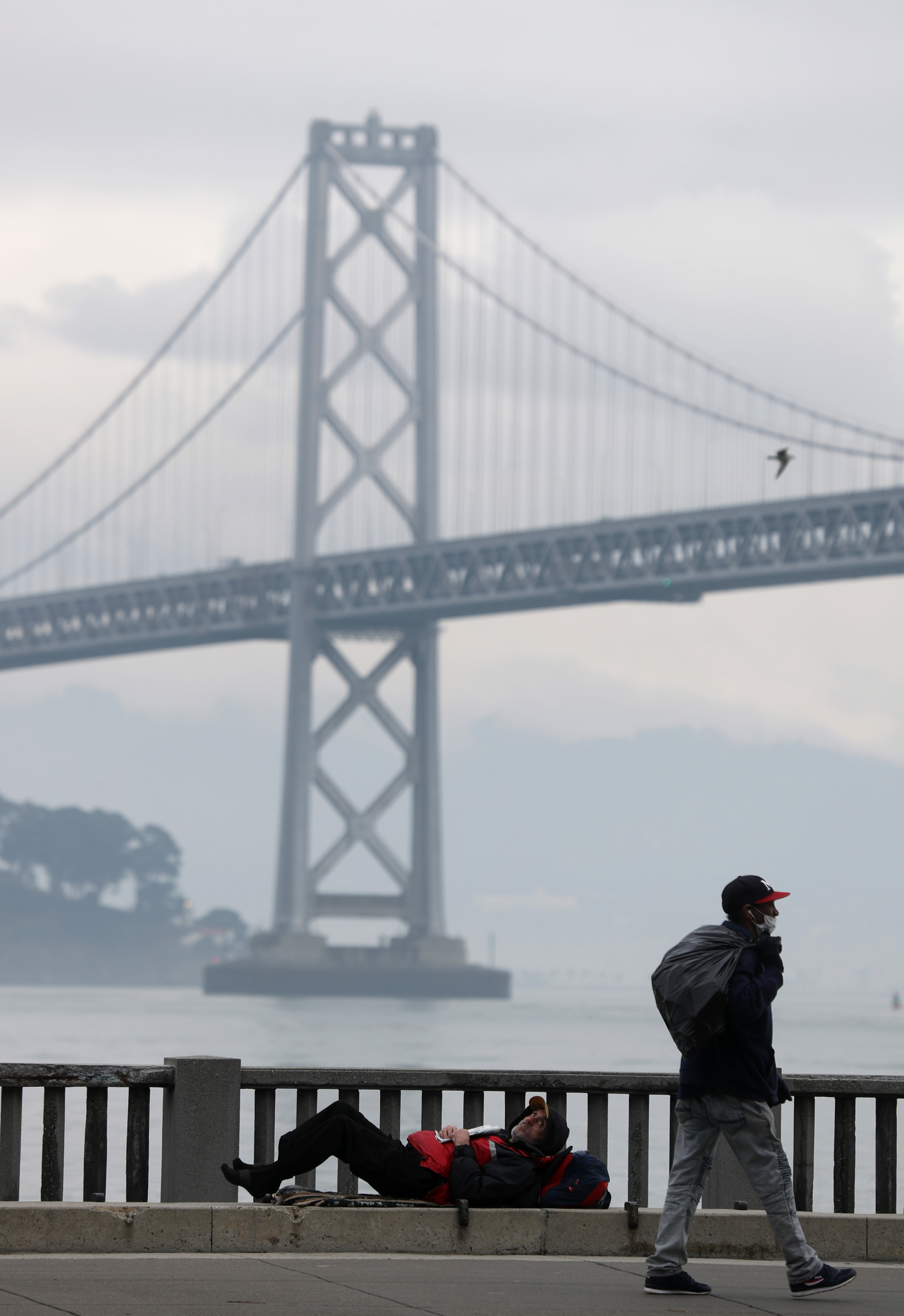 A homeless man lays on the sidewalk near the San Francisco–Oakland Bay Bridge on December 05, 2019 in San Francisco, California. (Photo by Justin Sullivan/Getty Images)