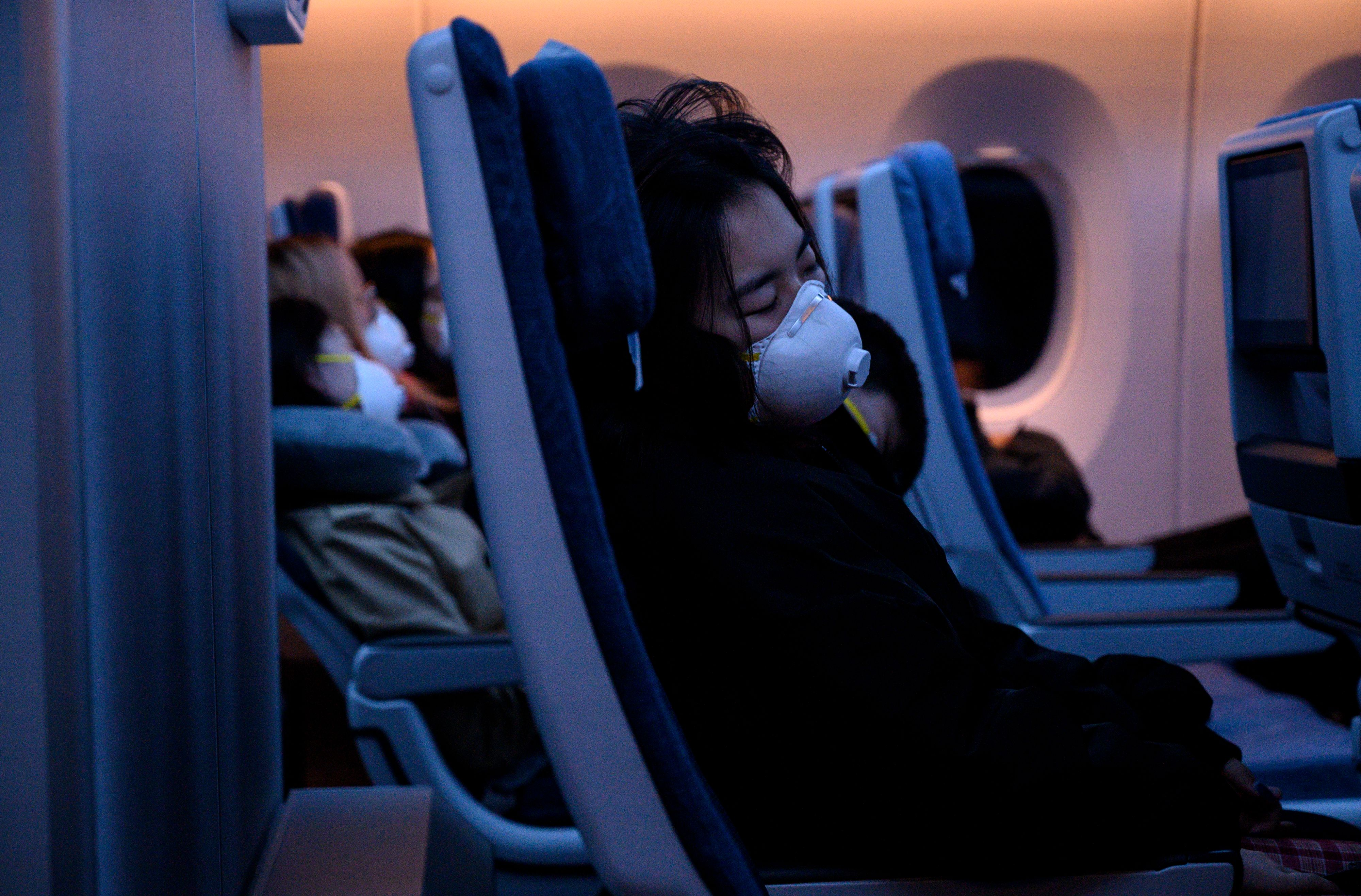 Passengers wearing protective face masks sleep on their flight to Shanghai on February 4, 2020. (Photo by NOEL CELIS/AFP via Getty Images)