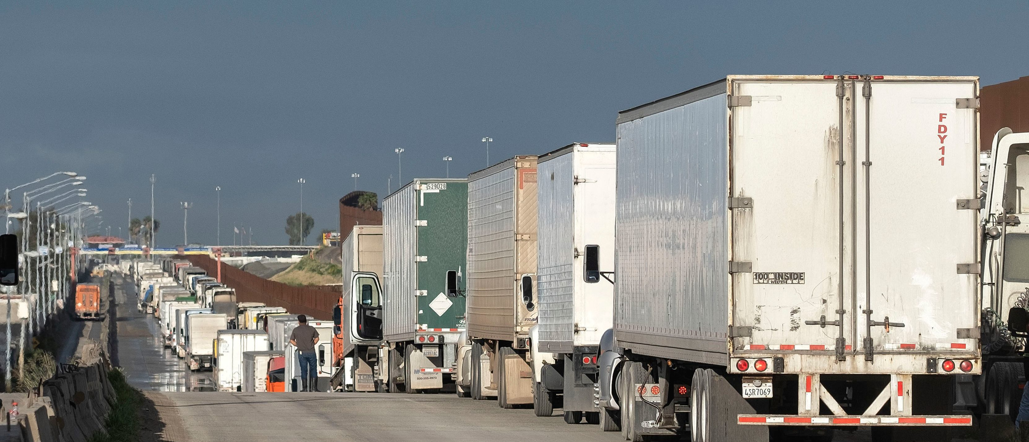 Trucks line up before heading to the United States at the Otay commercial port of entry on the US-Mexico border in Tijuana, Baja California State, Mexico, on March 20, 2020. - Mexico and the United States have agreed to 'restrict non-essential' border crossings in an attempt to slowdown the COVID-19 spreading, limiting the crossings to commercial, medical and essentials. (Photo by Guillermo ARIAS / AFP) (Photo by GUILLERMO ARIAS/AFP via Getty Images)
