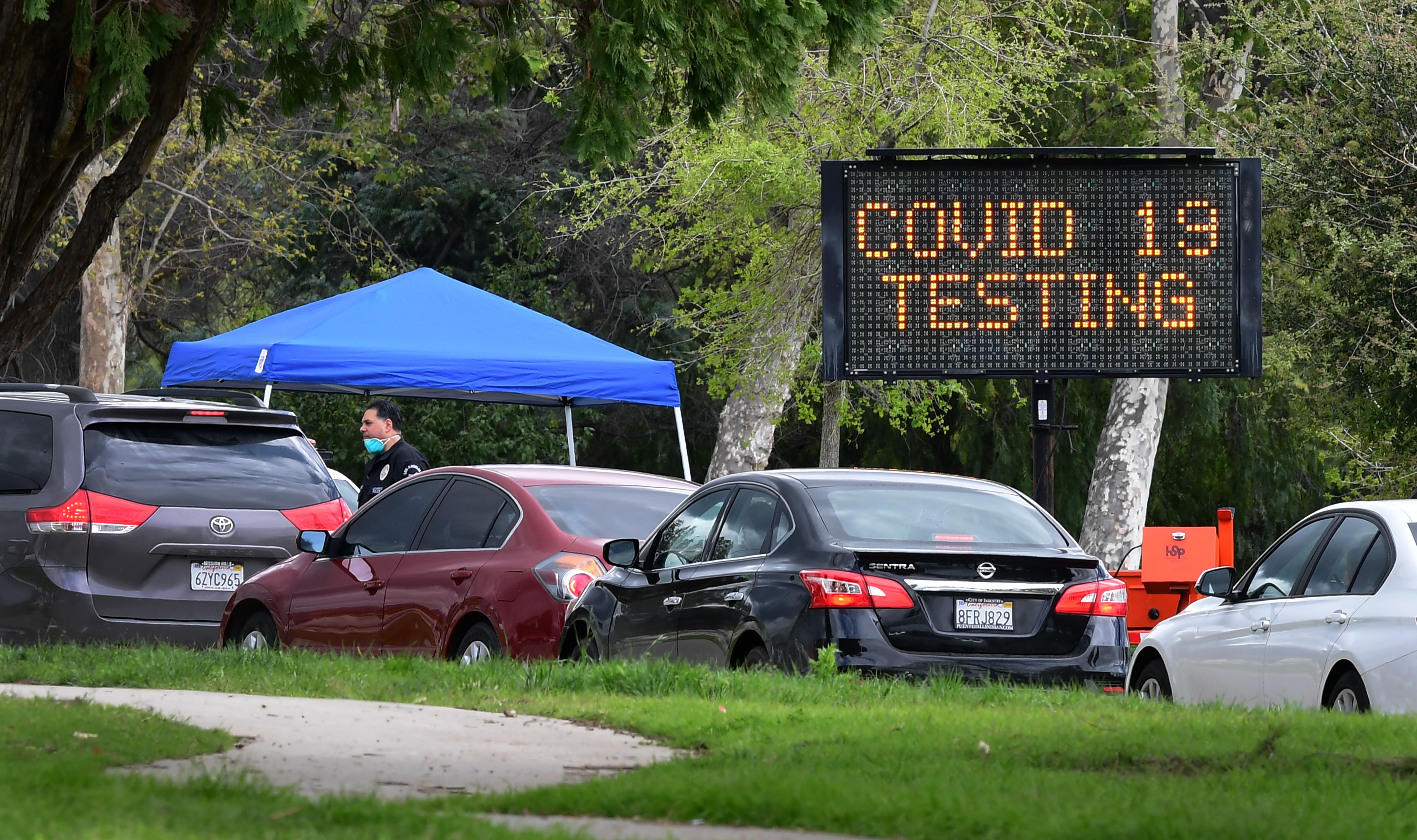 - A police officer mans the entrance to a coronavirus (COVID-19) testing center in Hansen Dam Park on March 25, 2020 in Pacoima, California. - California, the most populous US state, has been one of the worst-hit during the pandemic. At least 51 people have died, with more than 2,500 cases, according to a tally from Johns Hopkins University. (Photo by Frederic J. BROWN / AFP) (Photo by FREDERIC J. BROWN/AFP via Getty Images)
