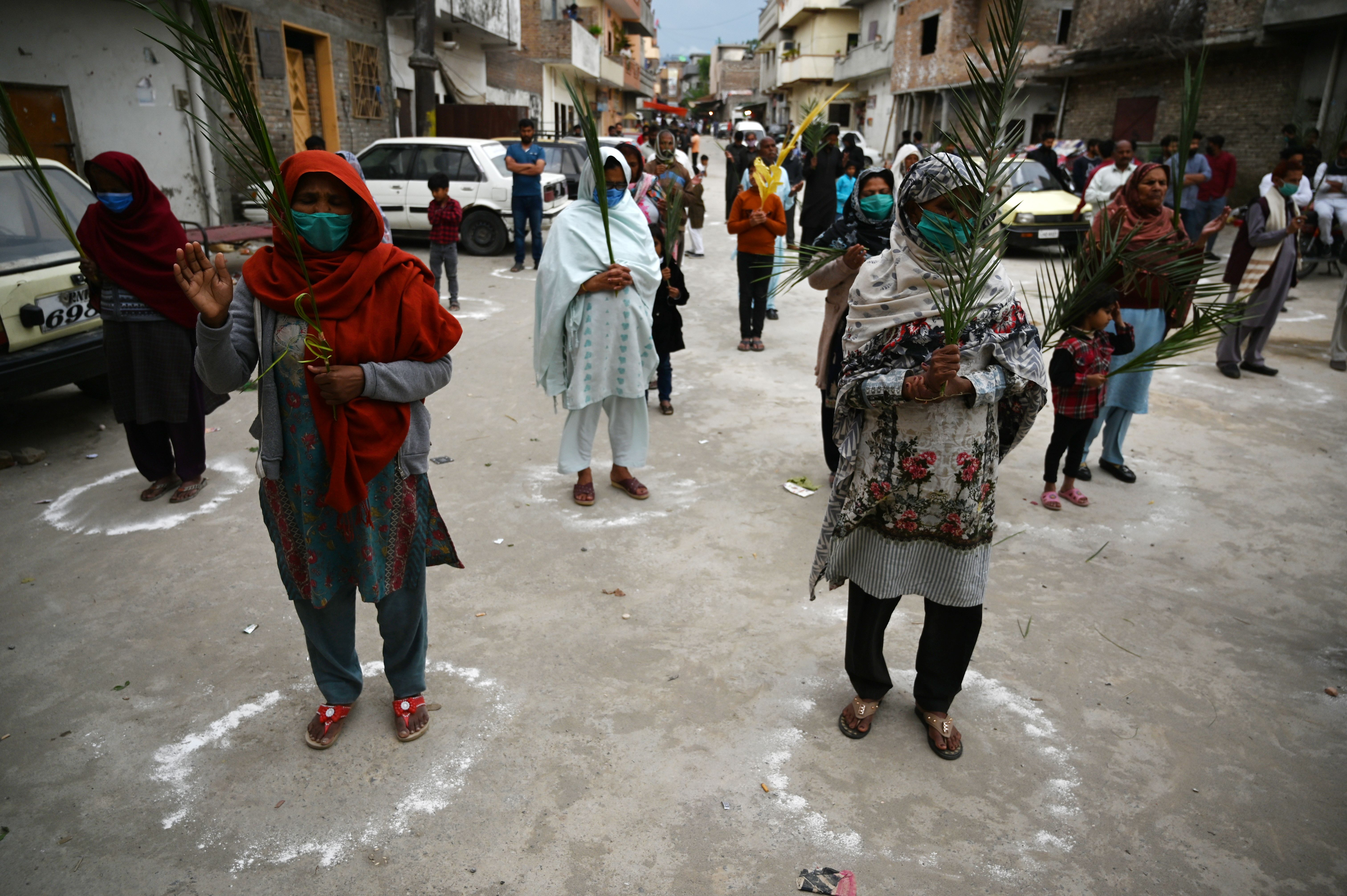 Christian devotees stand in circles marked on the ground to maintain social distancing as they hold palm branches to celebrate a Palm Sunday event at the Christian neighborhood during a government-imposed nationwide lockdown. (Photo by AAMIR QURESHI/AFP via Getty Images)