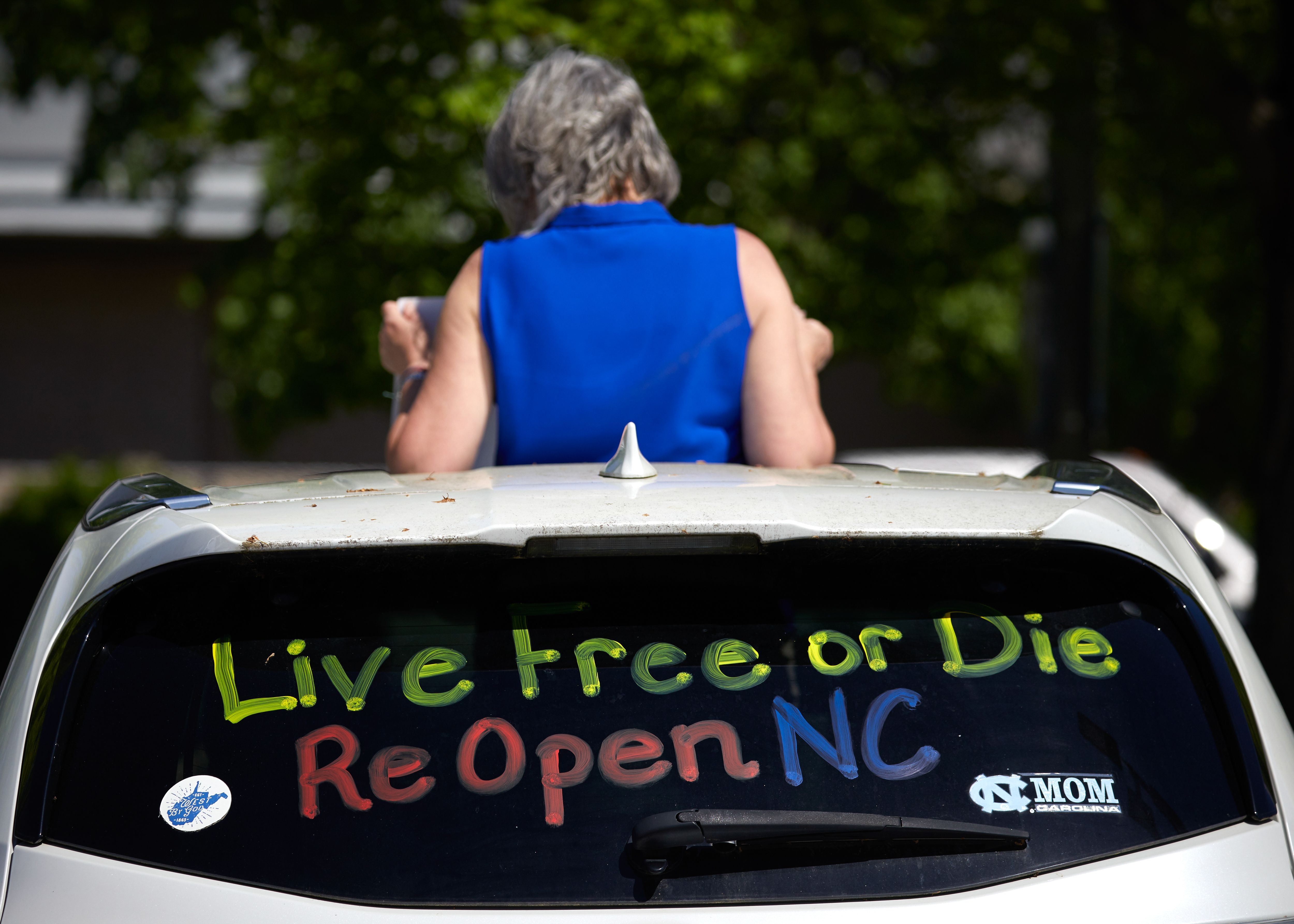 Protesters from a grassroots organization called REOPEN NC protests the North Carolina coronavirus lockdown at a parking lot adjacent to the North Carolina State Legislature in Raleigh, North Carolina, on April 14, 2020. - The group was demanding the state economy be opened up no later than April 29. (Photo by Logan Cyrus / AFP) (Photo by LOGAN CYRUS/AFP via Getty Images)